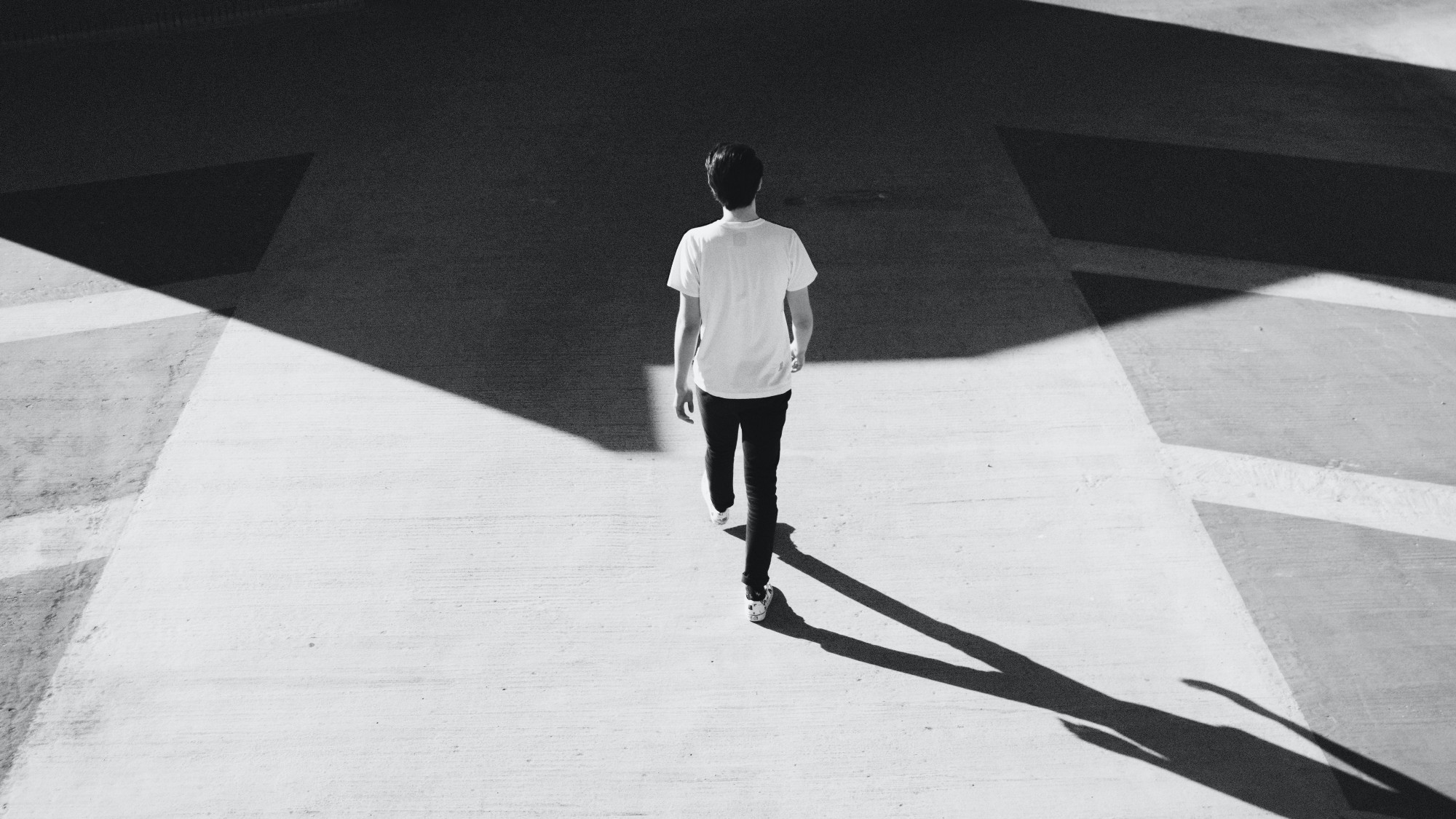 Person walking on concrete road, towards a shadow, image black and white