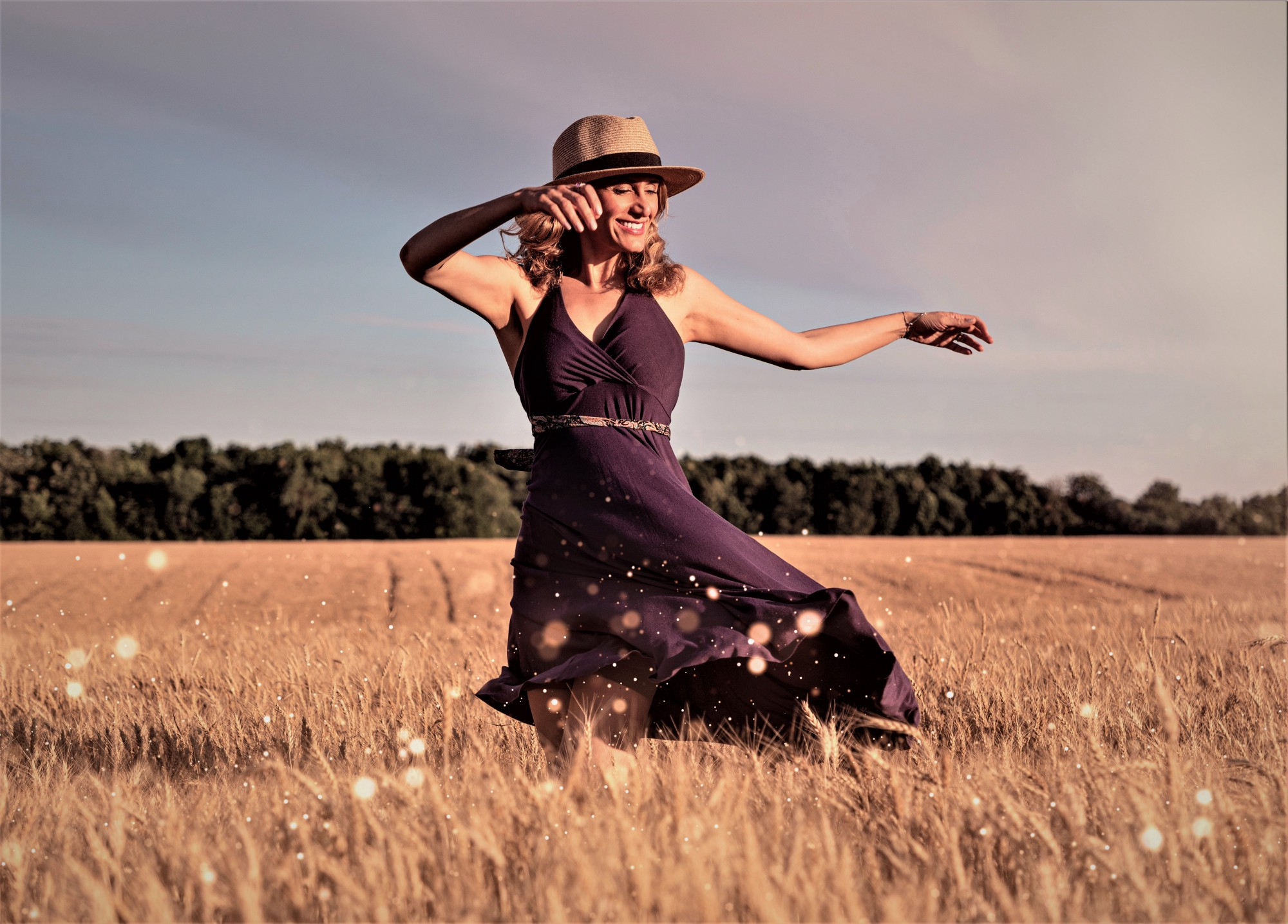 smiling woman wearing hat and brown dress dancing in field