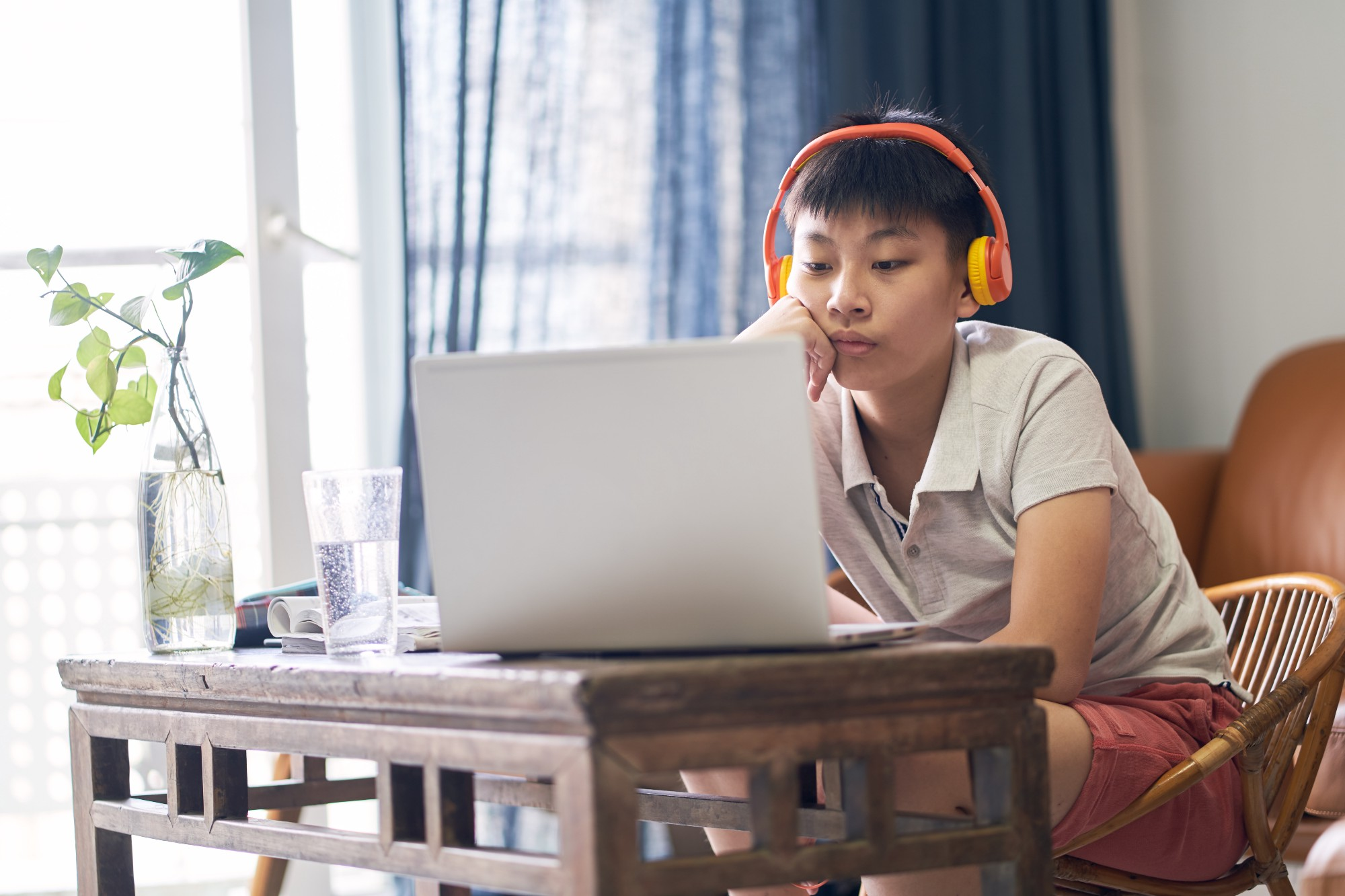 Young Asian boy using a laptop and headphones. Photo by allensima/Getty Images