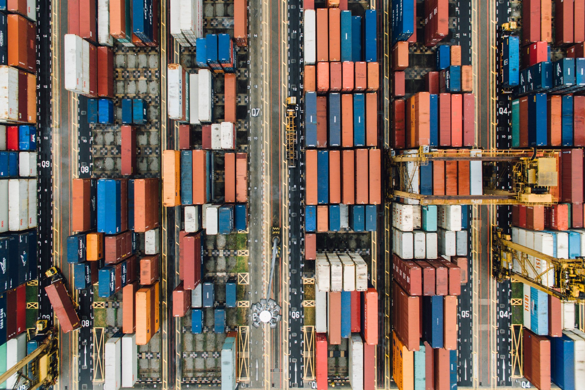 High traffic view of a ship yard showing many containers and coordination between them.