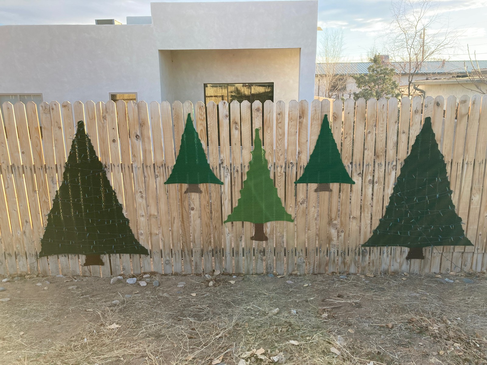 Five crochet trees on a fence