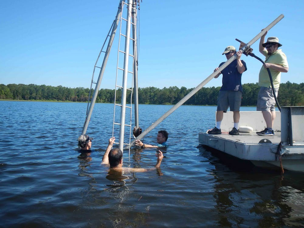 Three people swimming with a metal apperatus while two other researchers assist.
