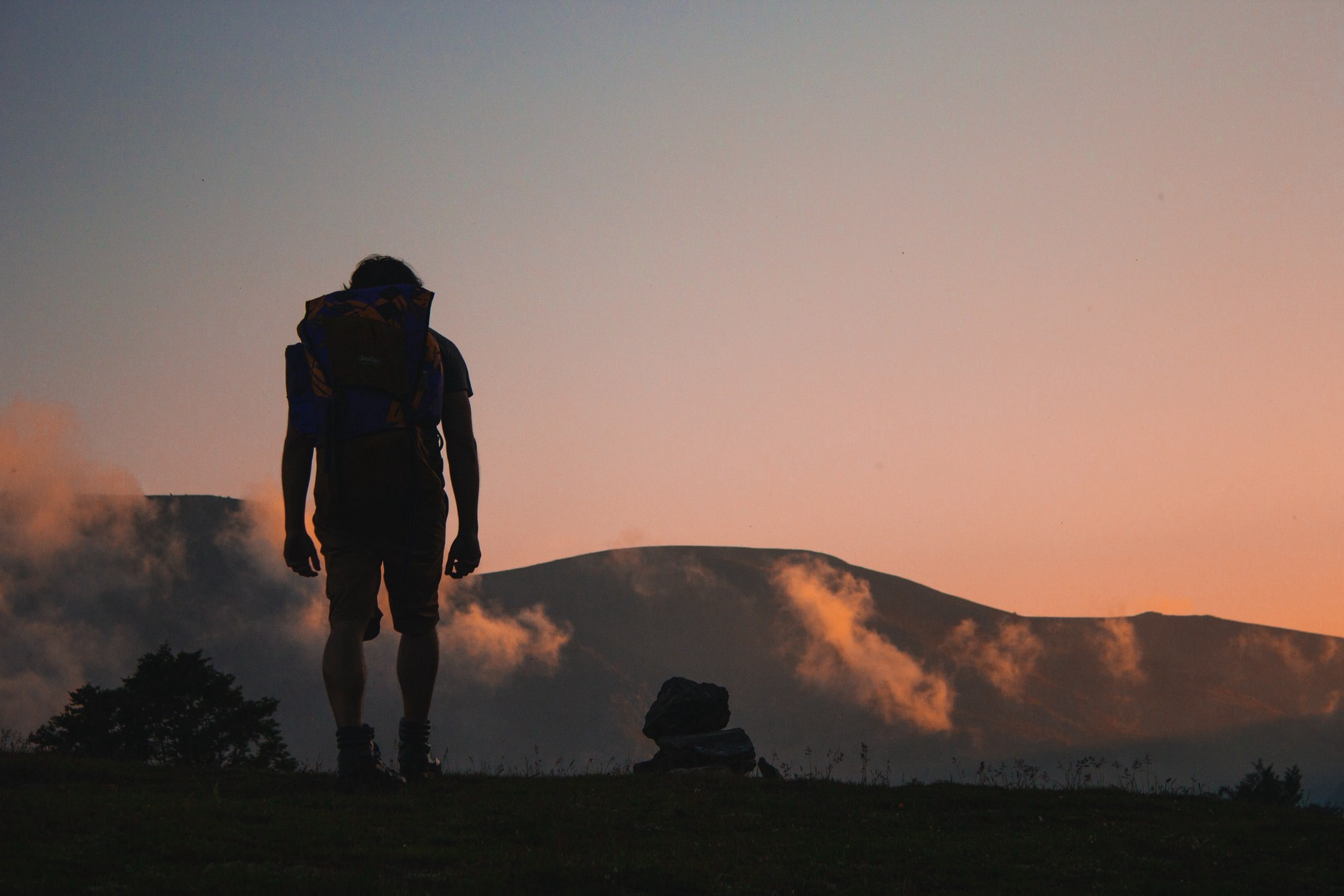 A silhouette of a person trekking towards an orange sky and large mountains.