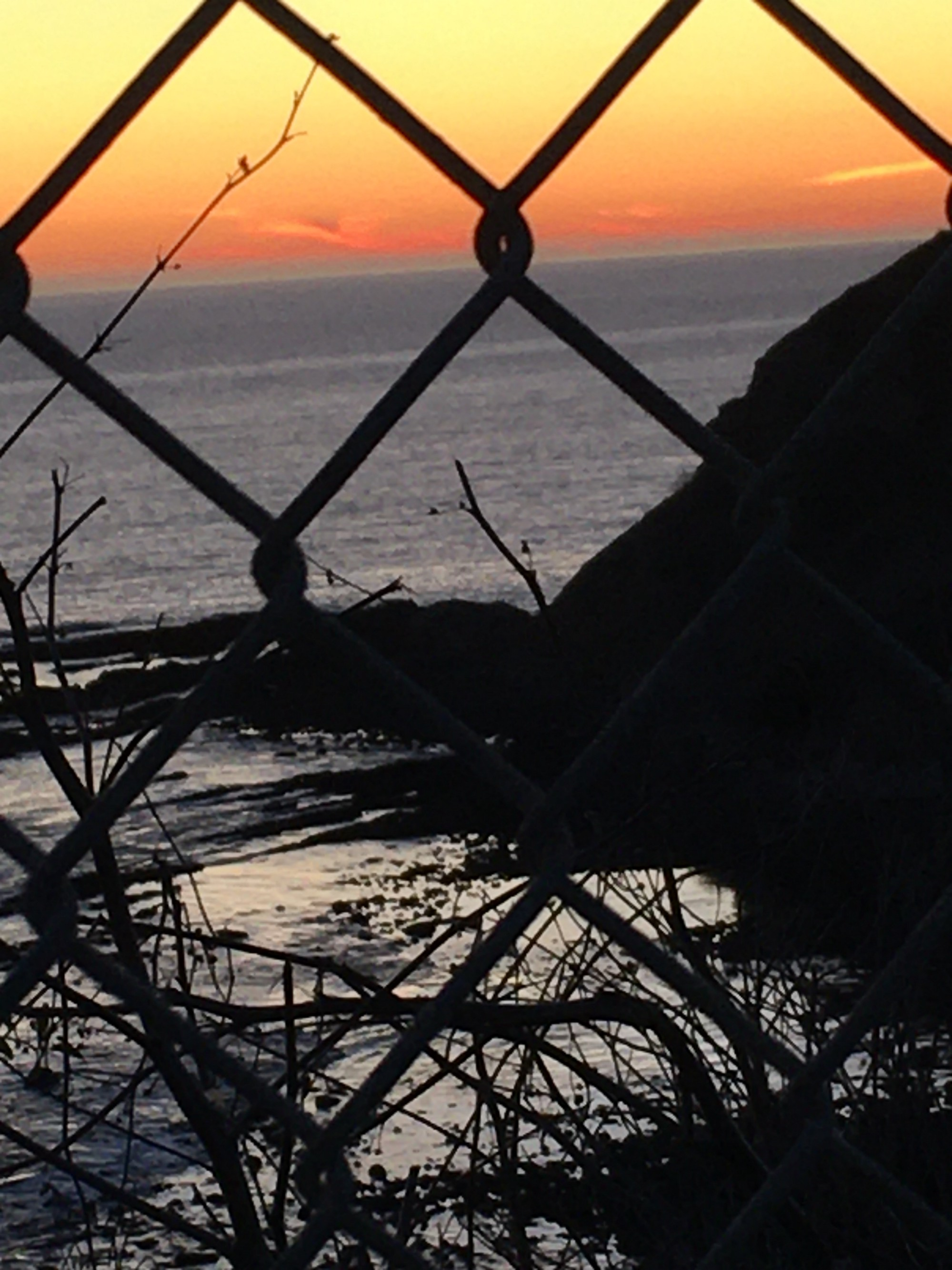 The ocean at sunset, orange layer below yellow layer, seen from behind a chain linked fence. In the foreground right is a hall, to the left of it sticks.