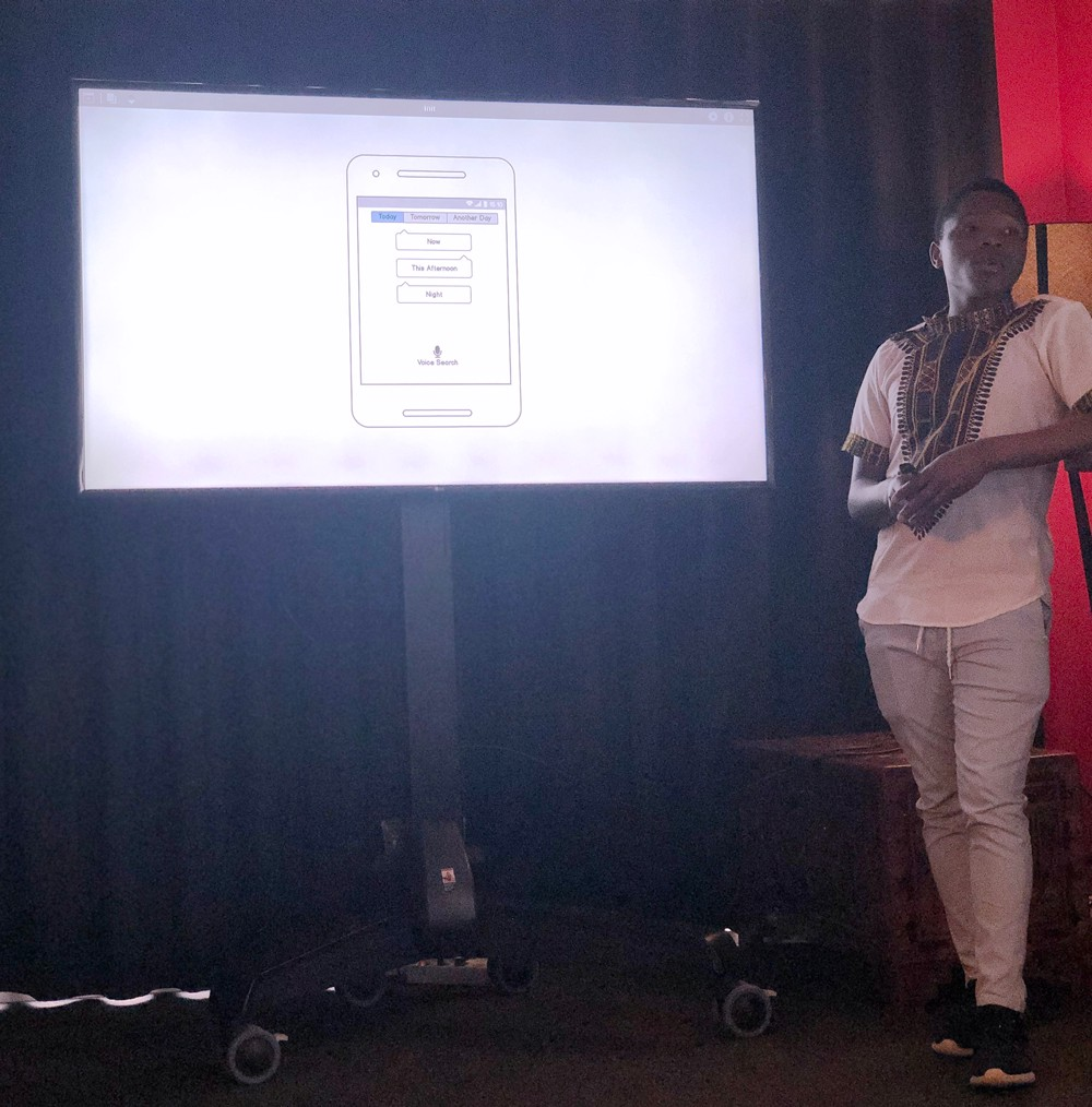 Student presenting in front of a screen which shows a mobile wireframe.