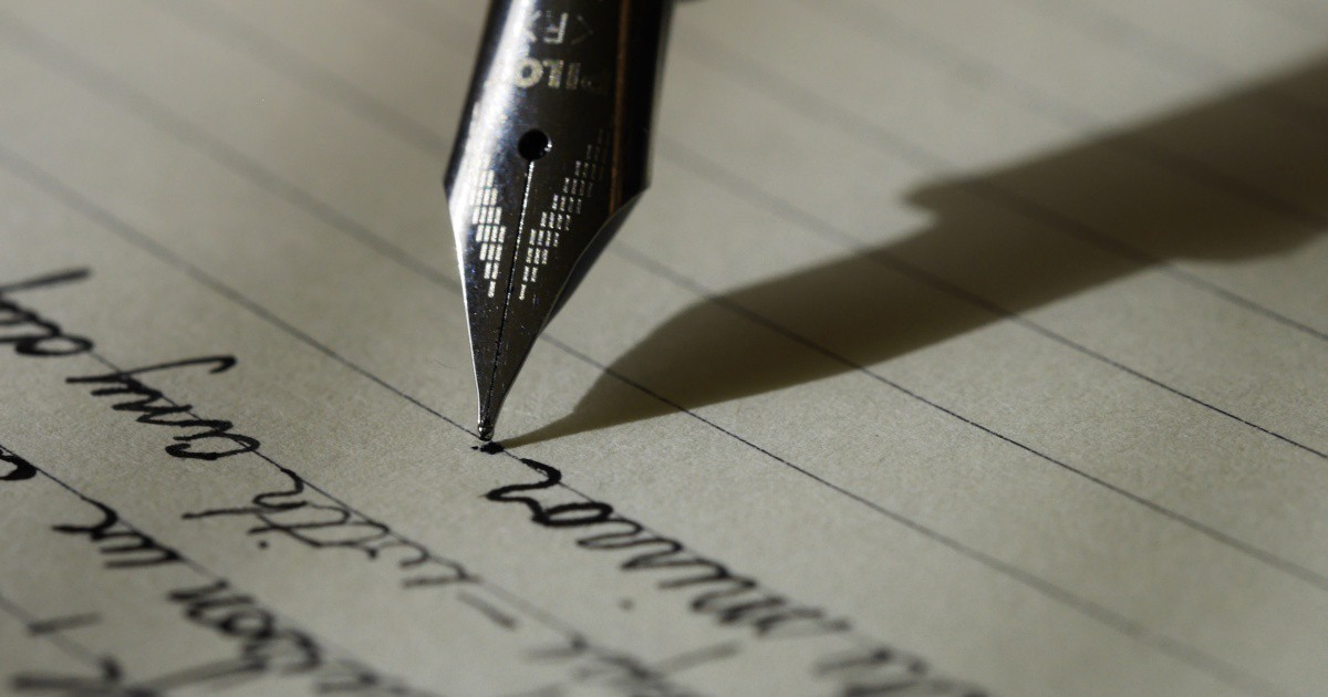 A close-up photo of a fountain pen writing in cursive on lined paper with black ink.