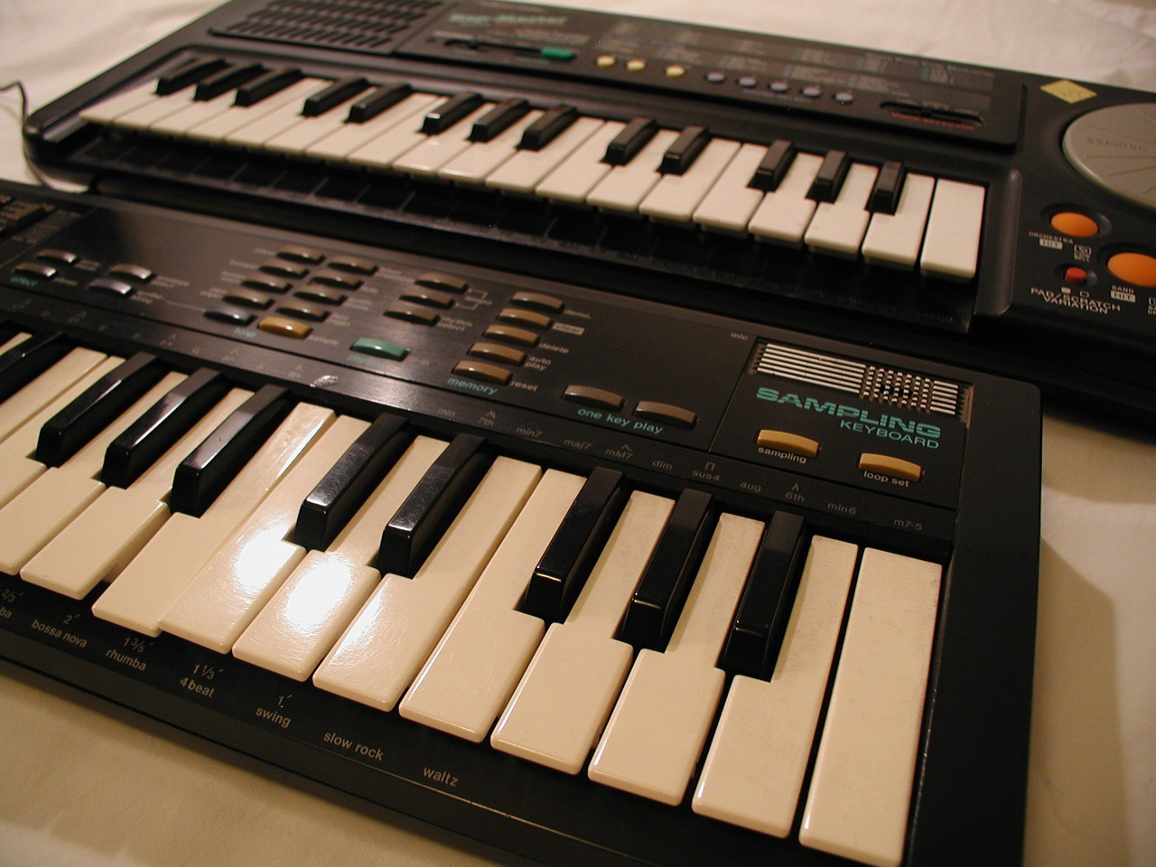 Photo of vintage mini-keyboards, forefronting the Casio SK-1 sampling keyboard of the 1980s