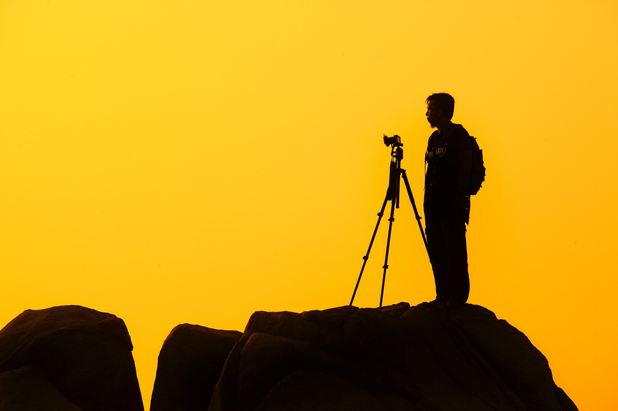 Photographer standing beside tripod silhouette with yellow background