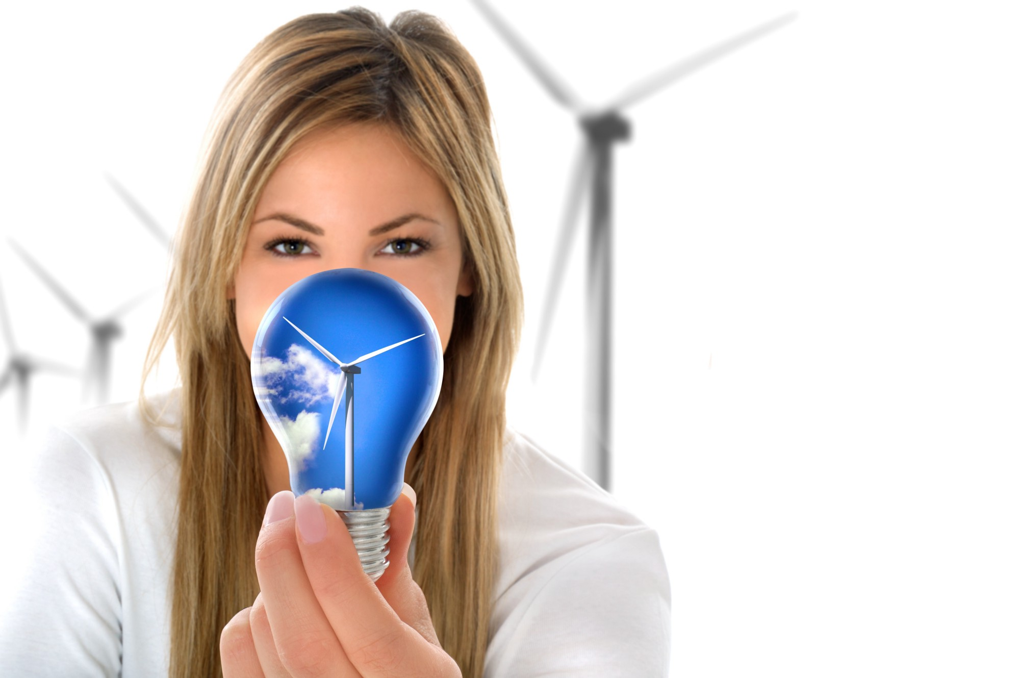 Woman holds light bulb in front of her with an image of a wind turbine inside