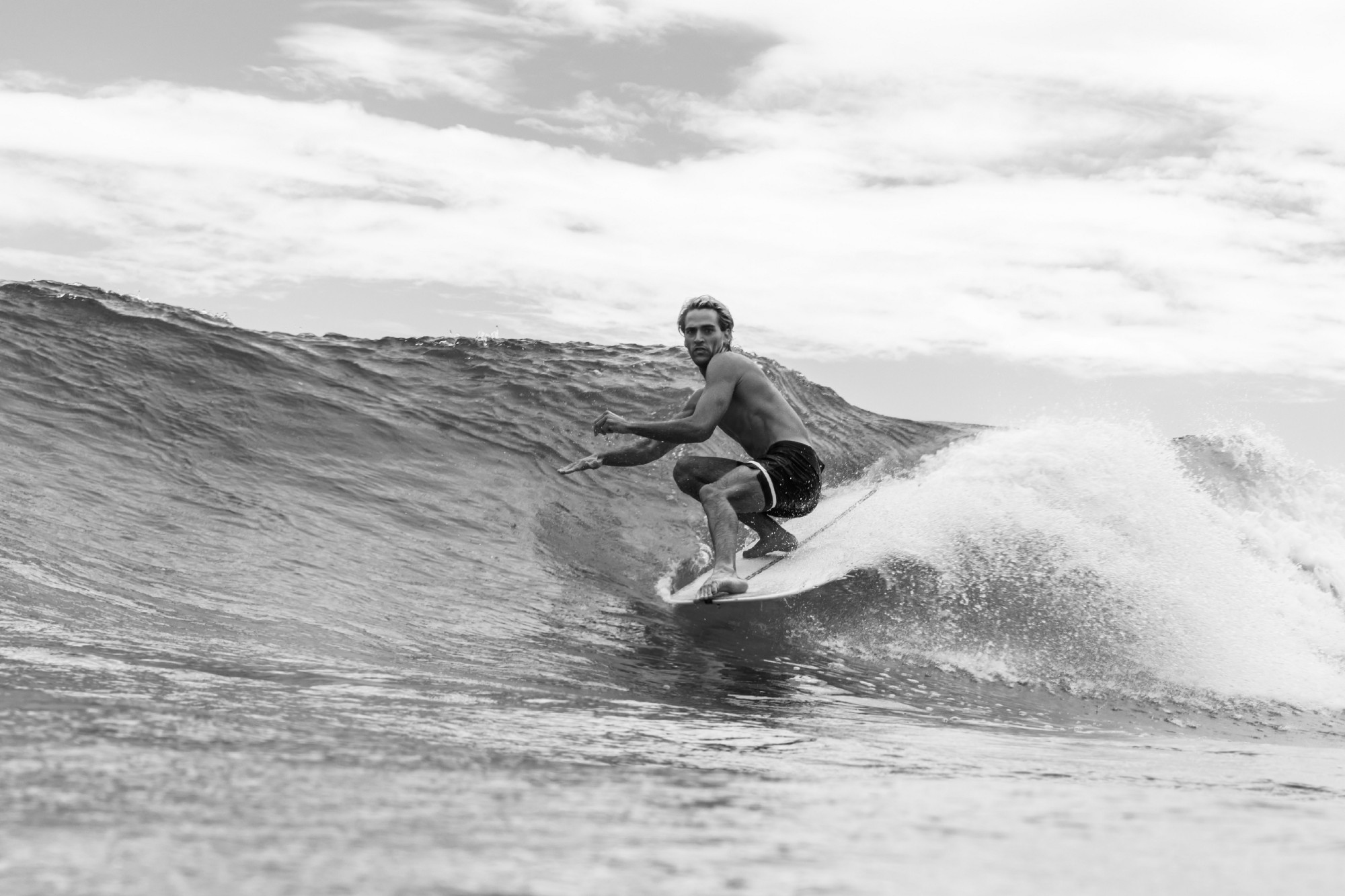 Black and white image of a shirtless muscular surfer