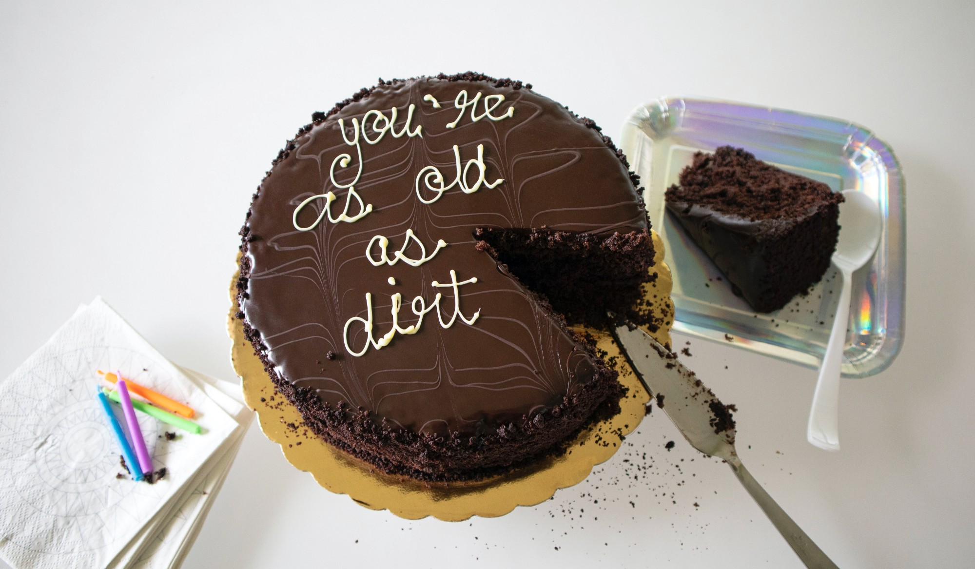 Chocolate birthday cake with the saying you're as old as dirt written on it with icing.