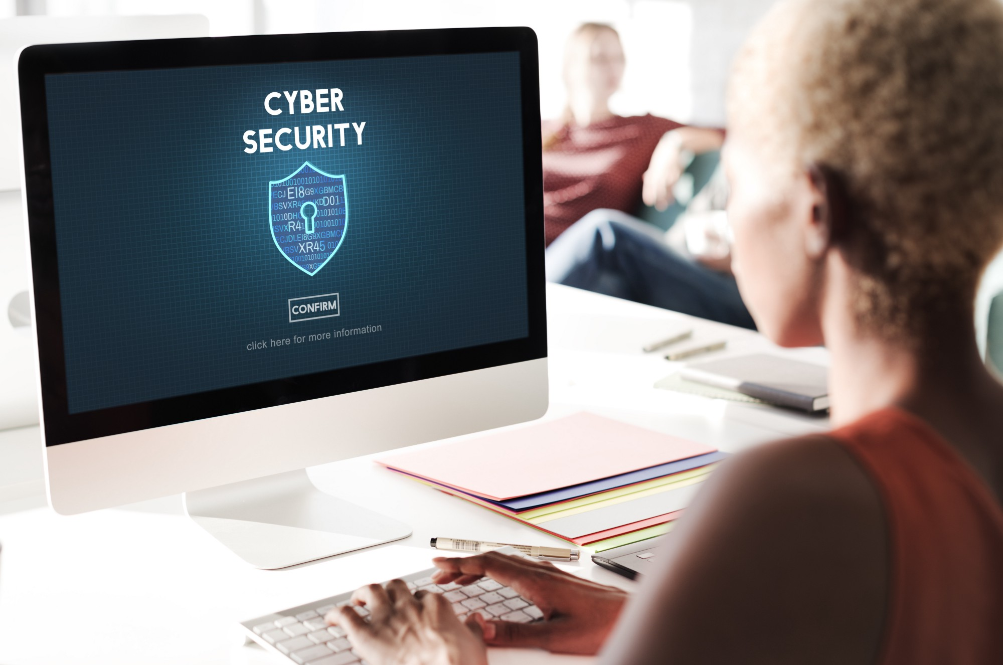 Cyber security protection firewall interface concept—meaning a blond girl with short hair sits in front of a computer screen with the word cyber security written on it.