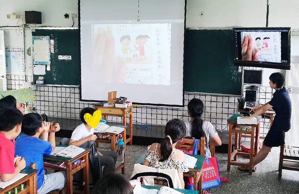 A teacher displaying a Mandarin textbook to the entire class with the Ziggi-HD Plus.