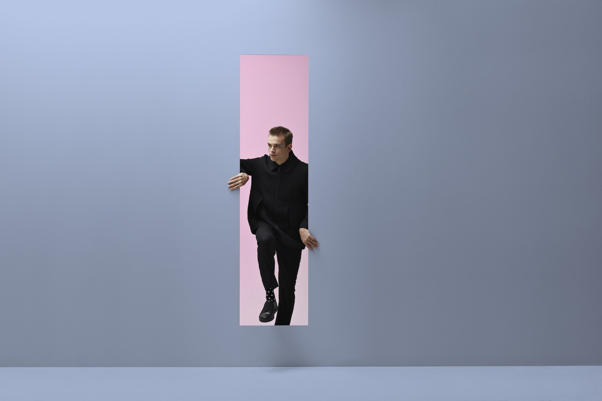 A masculine-appearing person emerging from a pink room into a blue room through a vertical rectangular opening in the wall.