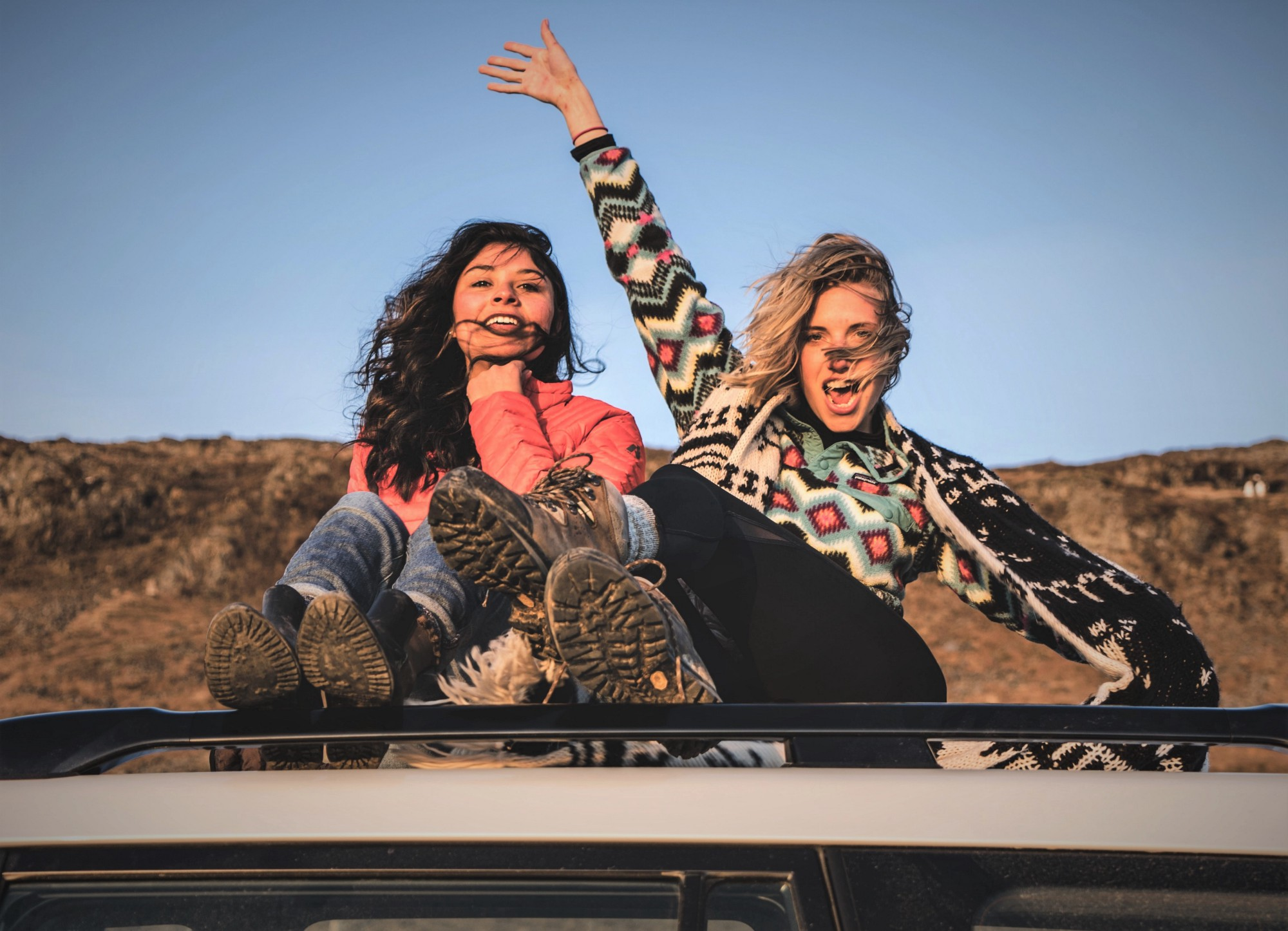 Two girls sitting on top of vehicle with wind blowing in their hair