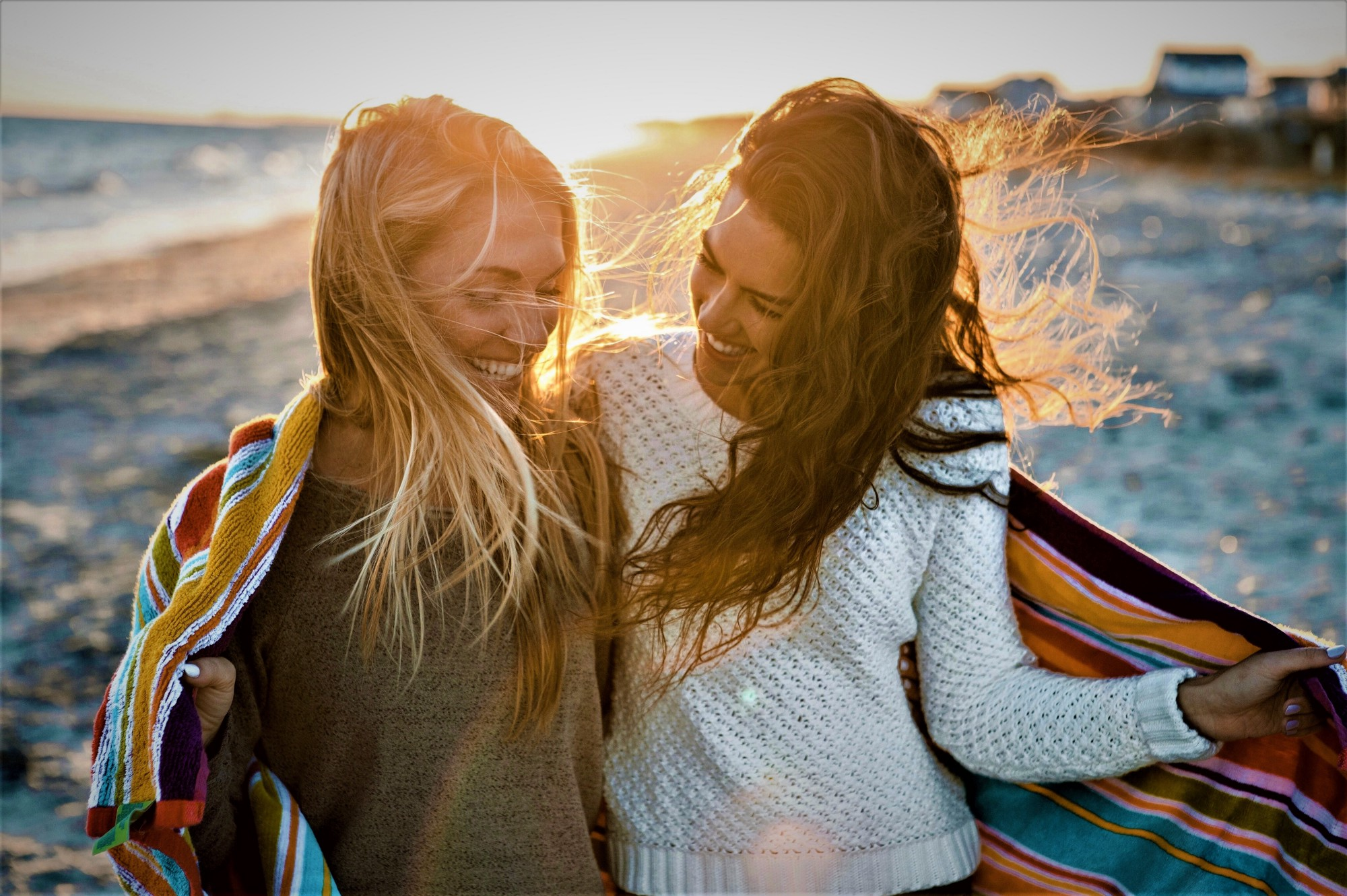 two smiling girls walking down beach with towel wrapped around them