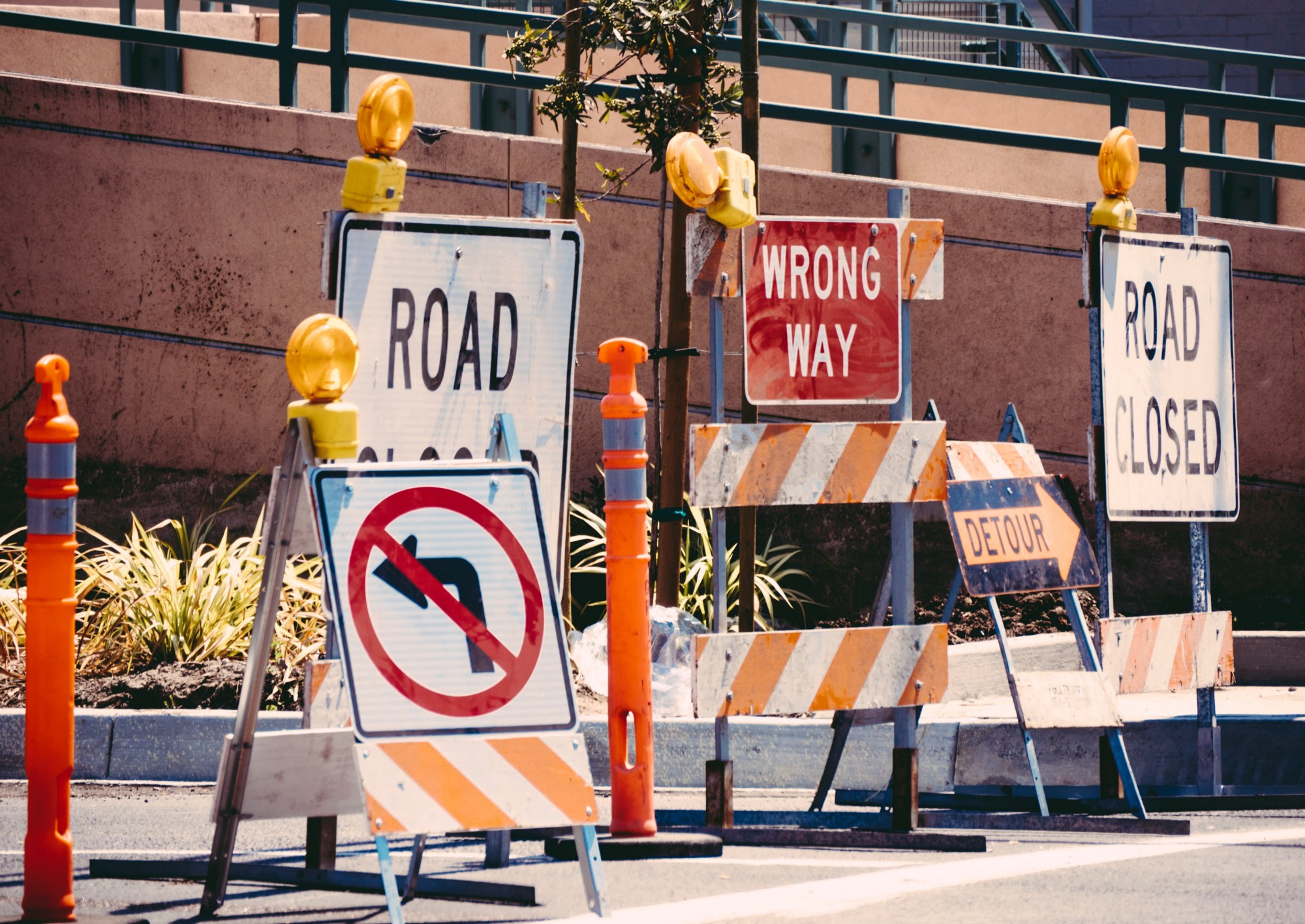 """A collection of signs on a street which read """"Road Closed, Wrong Way, No Left Turn, and Detour."""""""