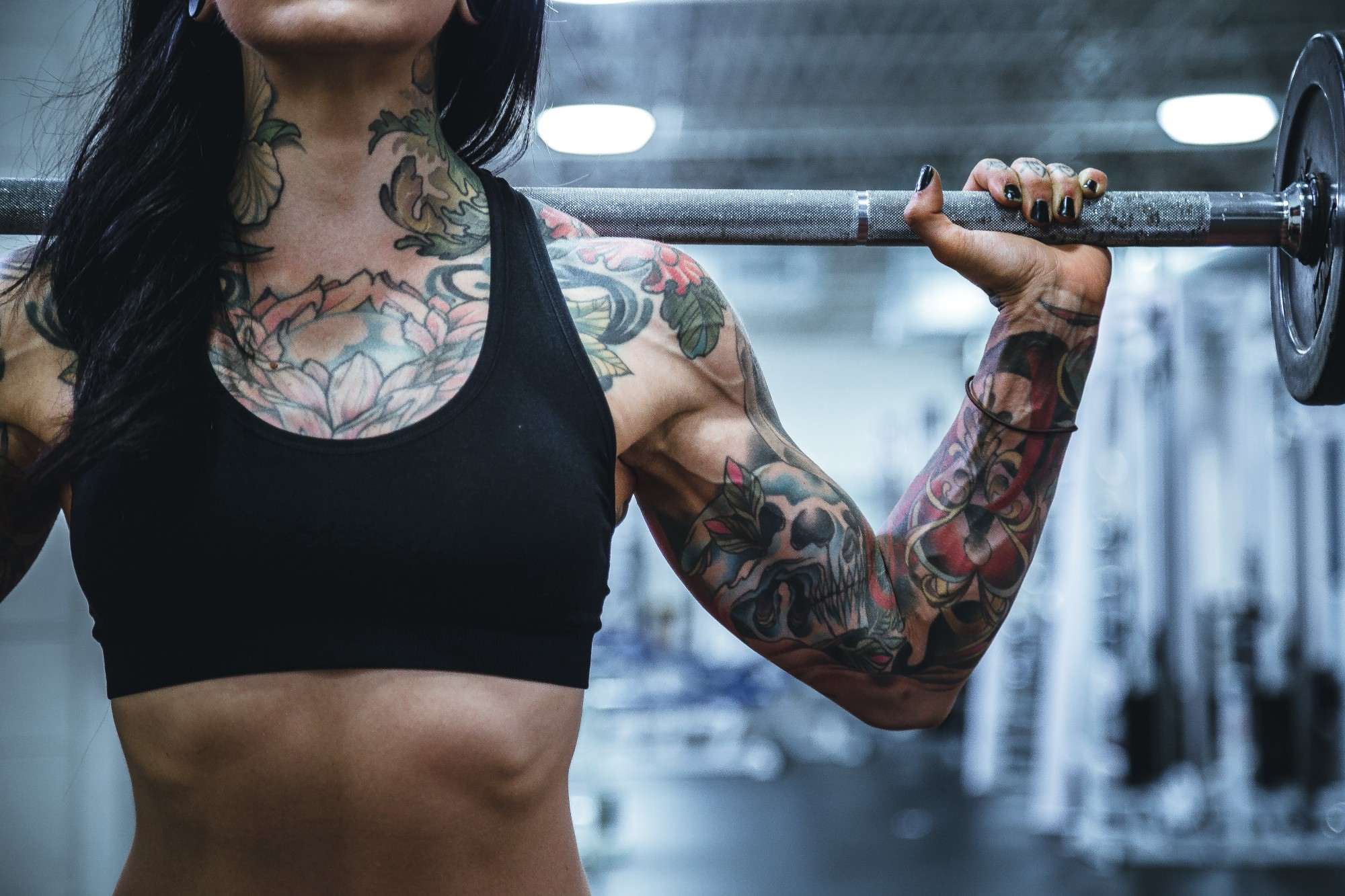 Photo of the torso and arm of a heavily tattooed woman lifting a weight