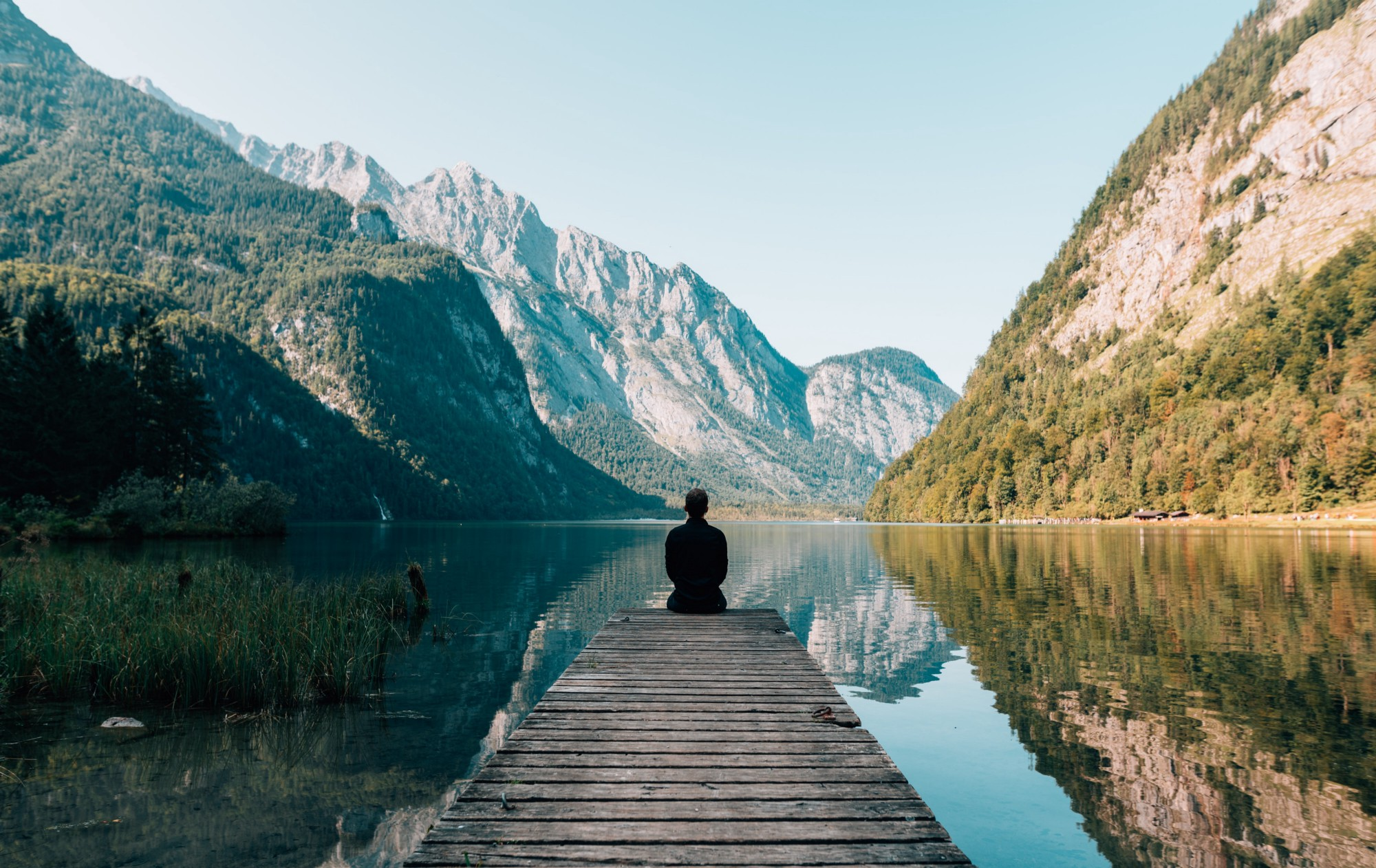 Lake view with mountains in the background. Man sitting on dock alone.