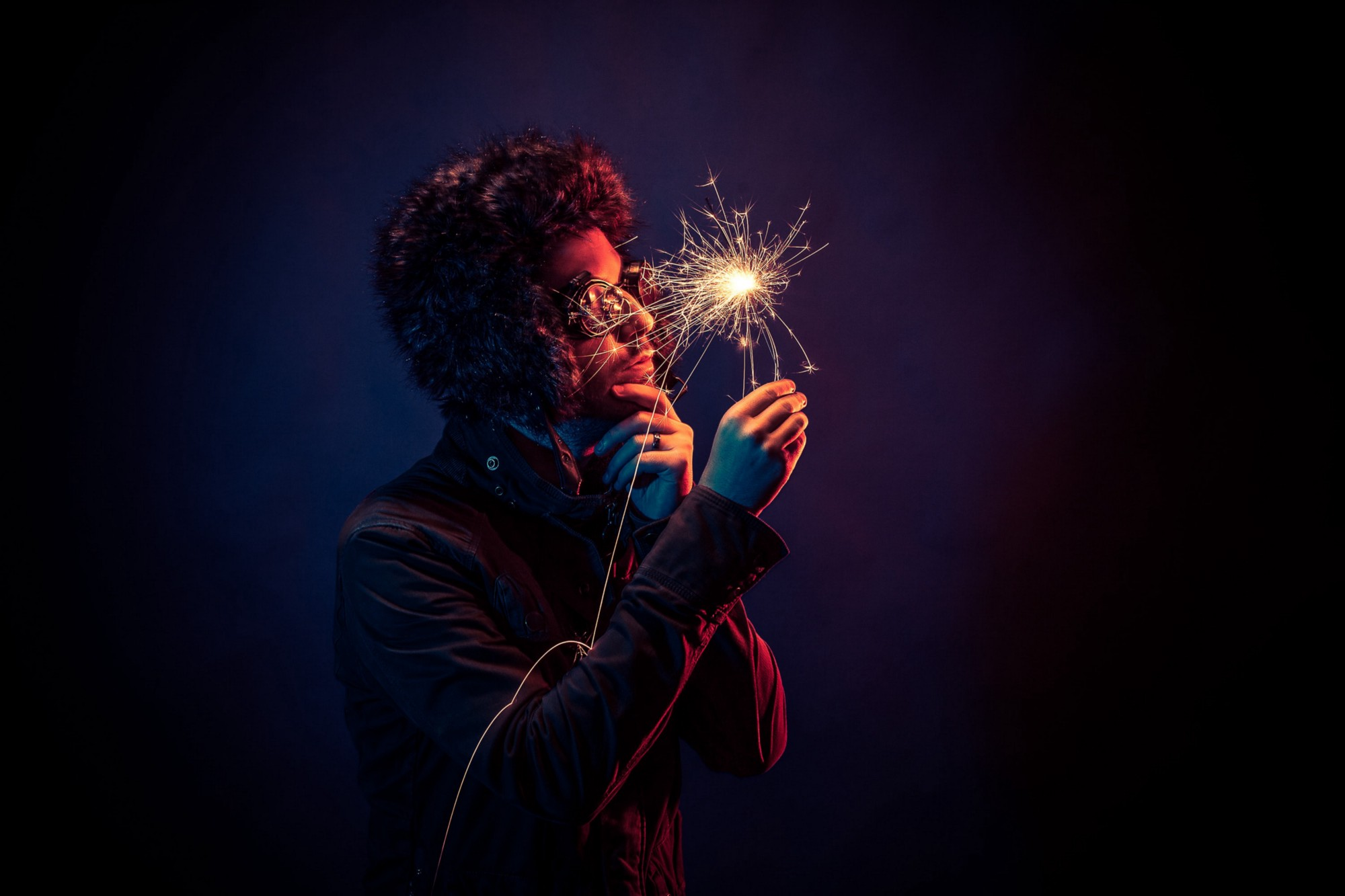 A man with a furry hat holding a sparkler.