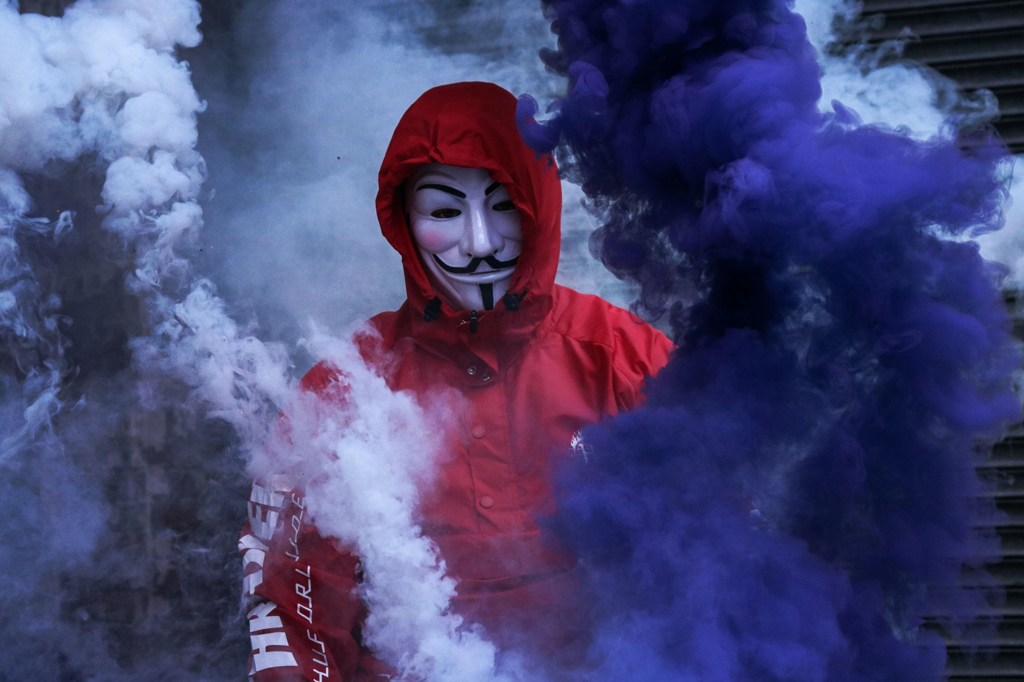 A person in a red jumpsuit wearing an anonymous mask.