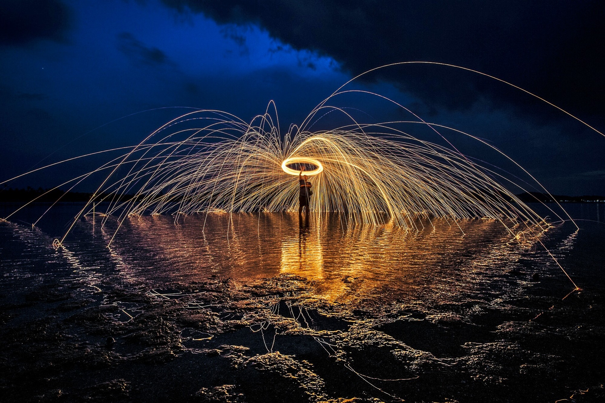 A man stands in water at night, spinning a ring of fire above his head, with sparks flying off.