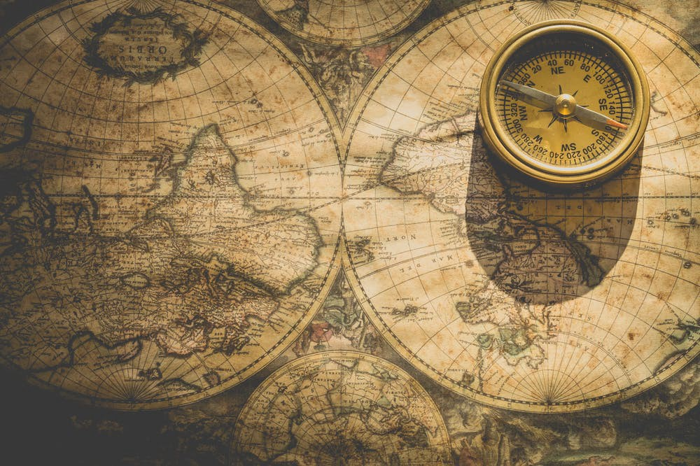 beige analog compass on old world map