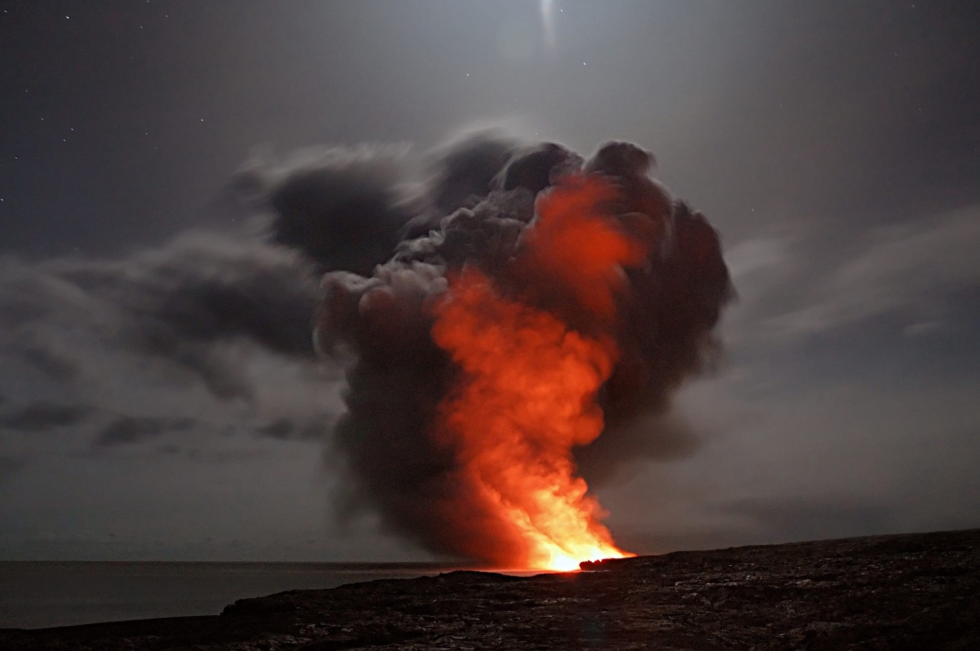 A red fire with smoke billowing from it burns against a grey sky.