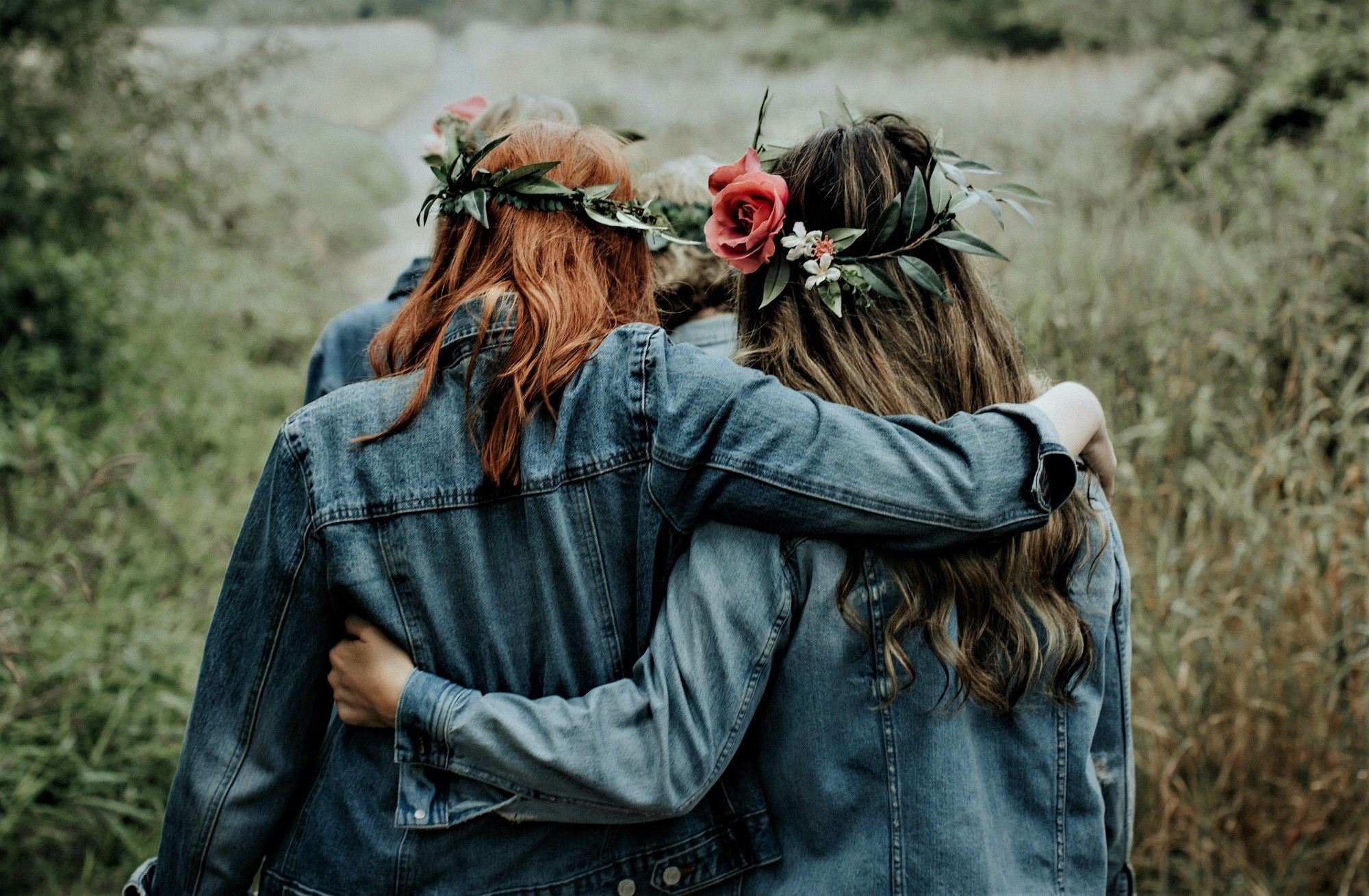 back view of two girls wearing denim jackets and flowers in their hair with arms around each other