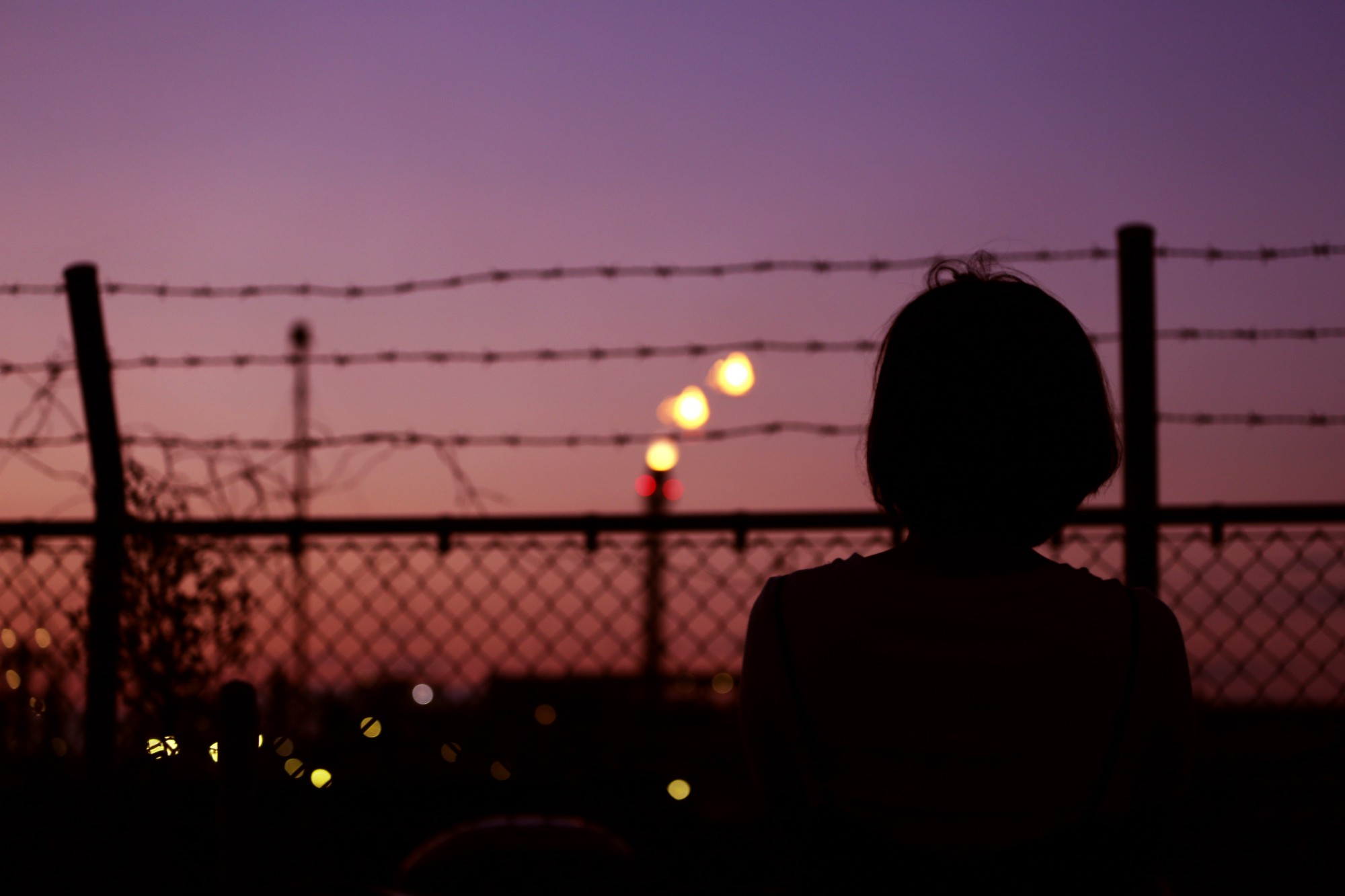 Silhoutted of person turned away and looking through chain-link fence with barbed wire into colours of sunset.