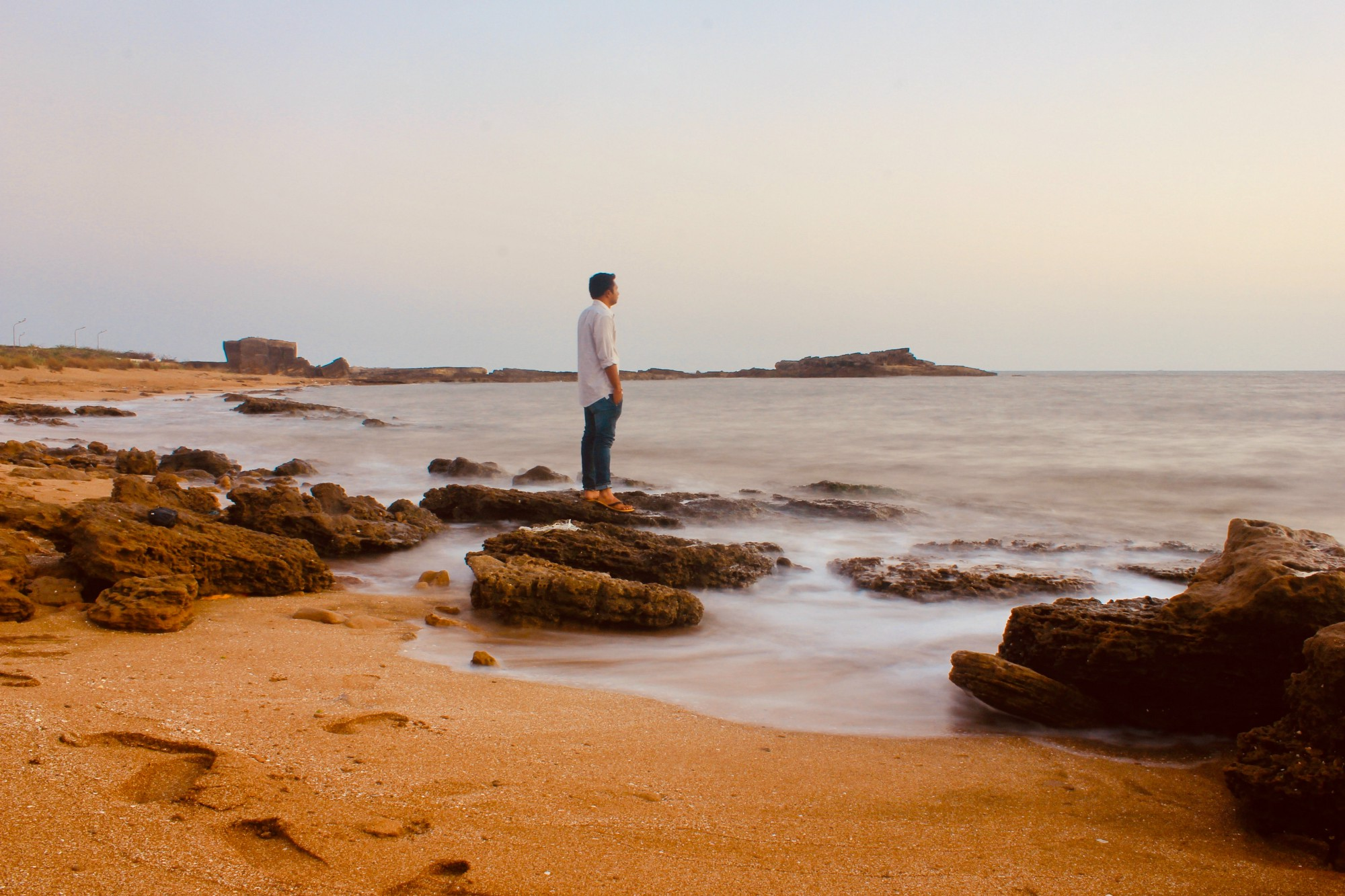 A man in a white shirt and jeans standing on rocks along a beach