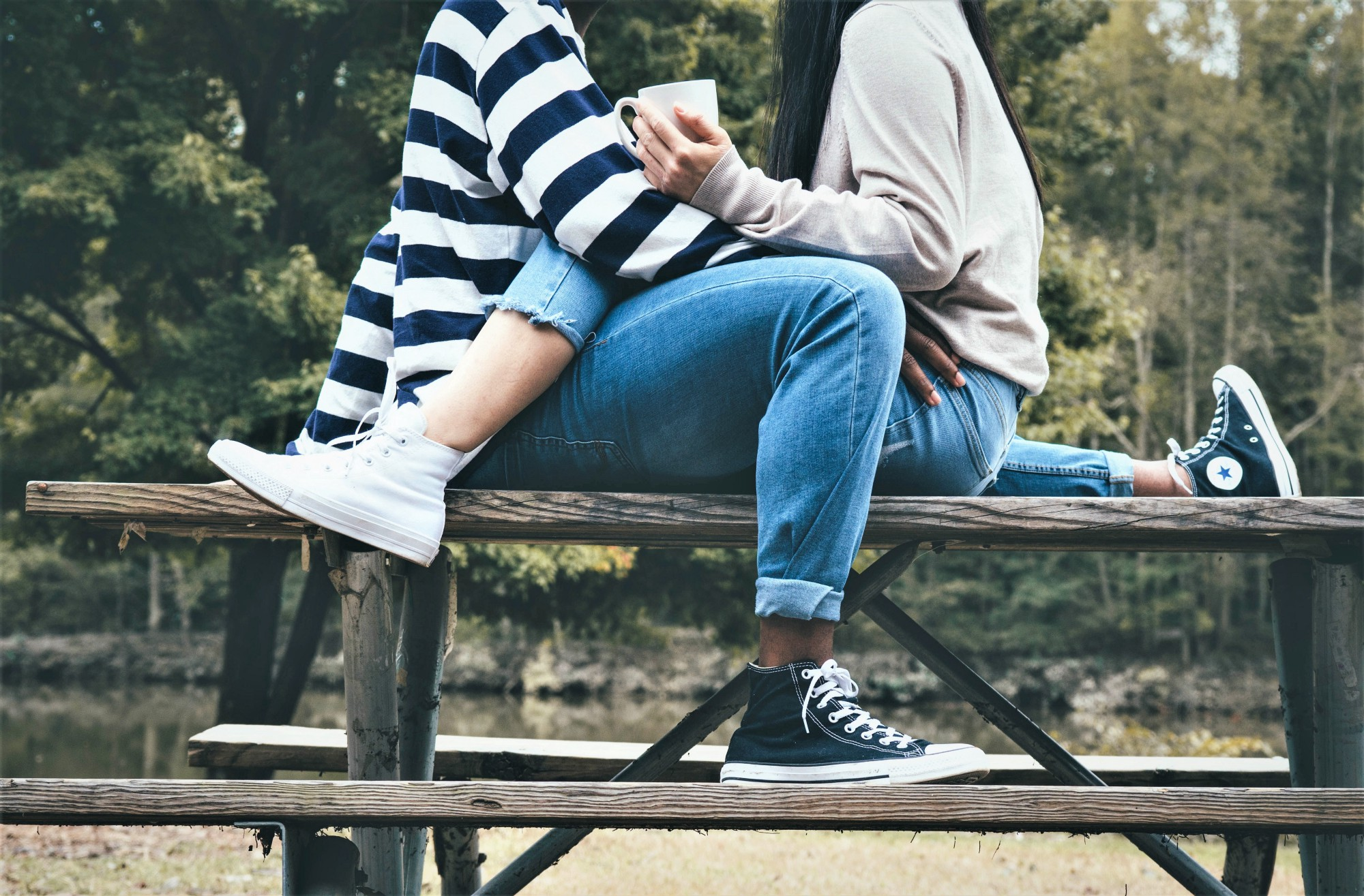 Couple sitting on picnic table facing each other with interlaced legs