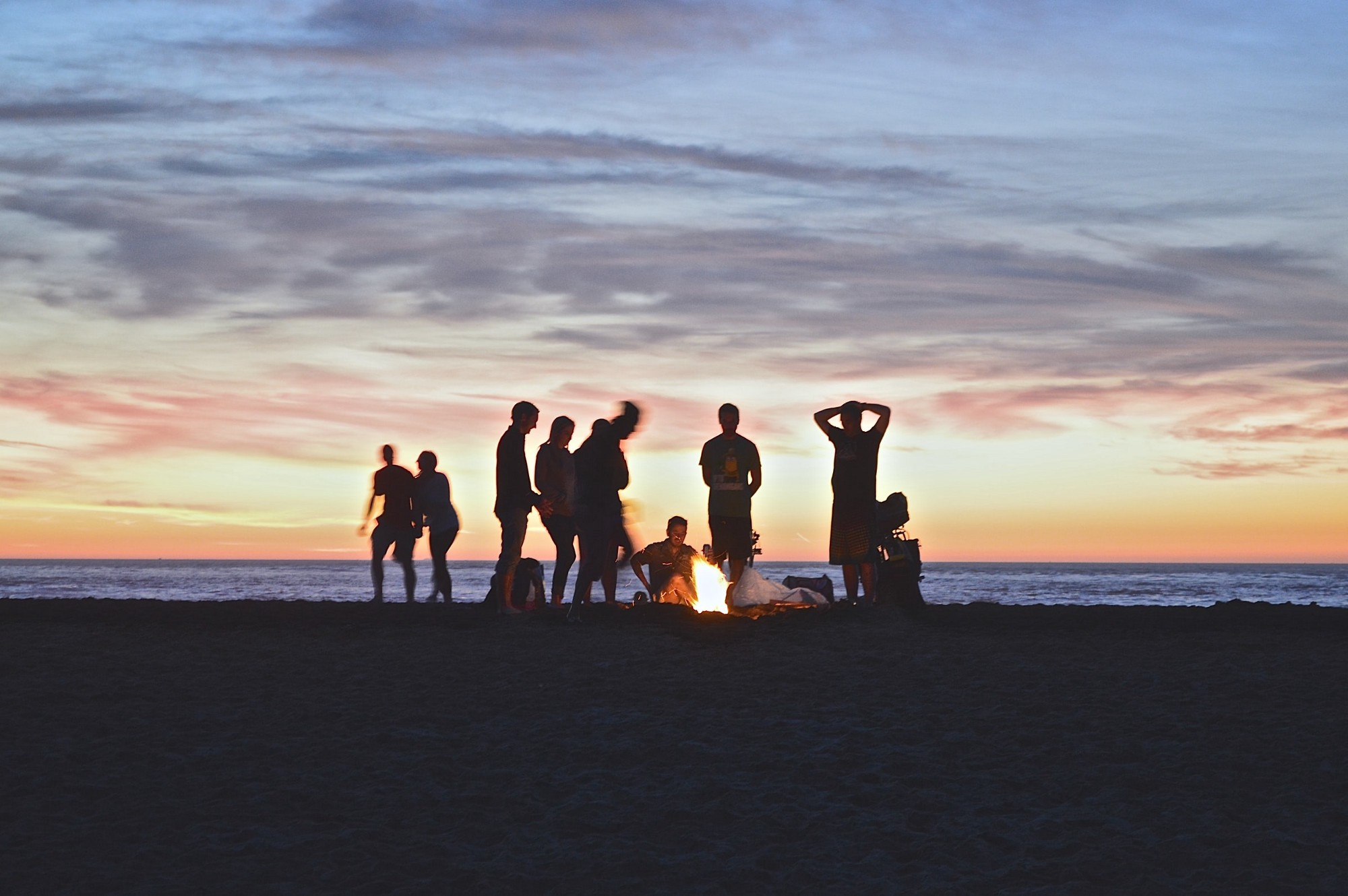 Friends at a beach bonfire.