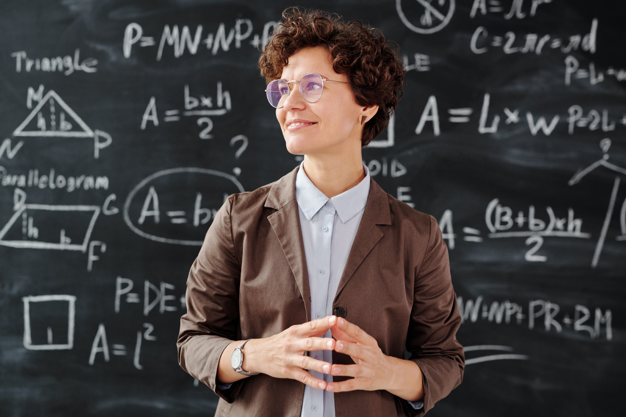 woman in brown blazer wearing sunglasses in front of a blackboard full of mathematical formulas