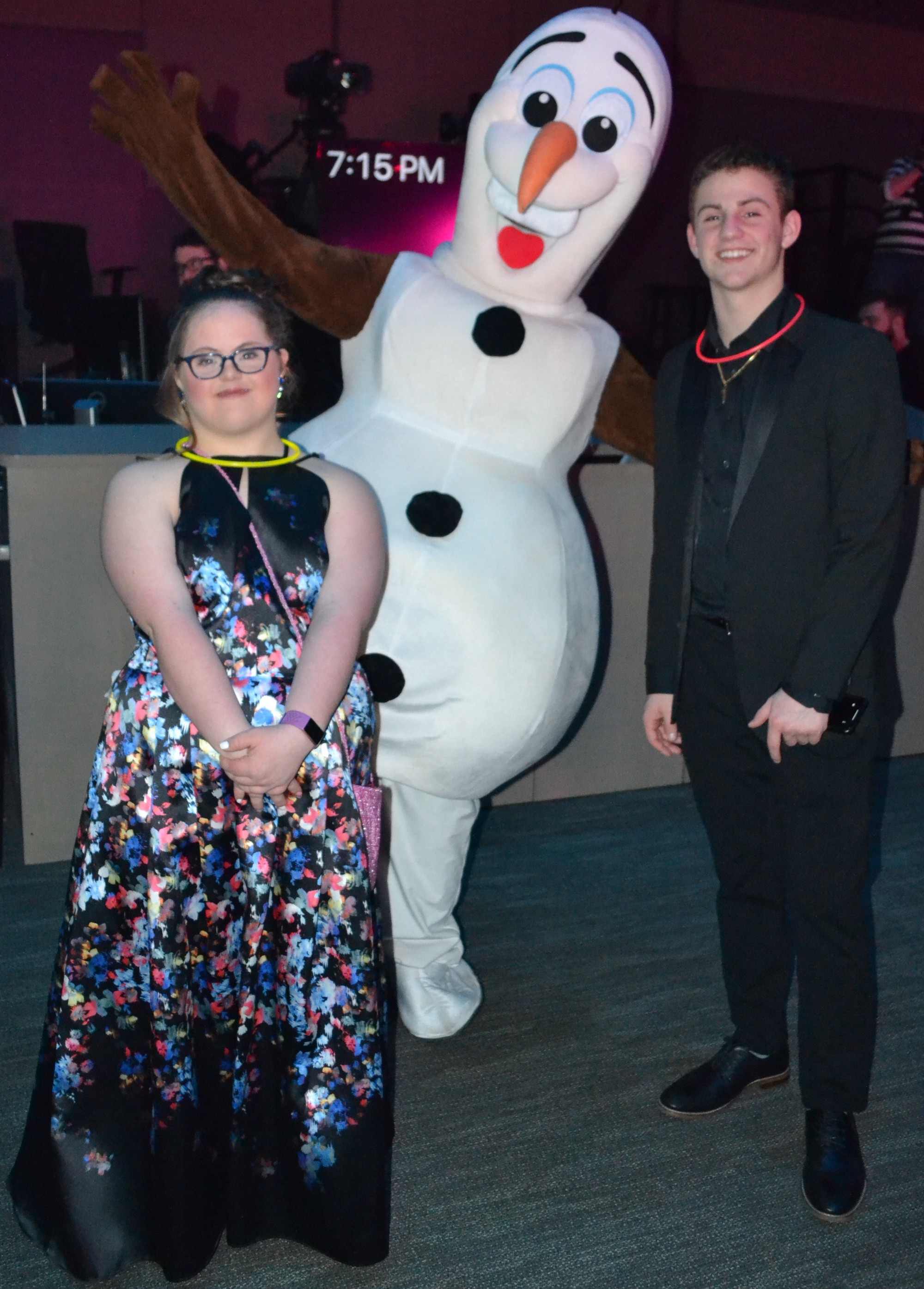 (left to right) Sarah Grace wearing a floral ball gown, Olaf (charchter from Frozen), and her brother Mathew wearing a suit