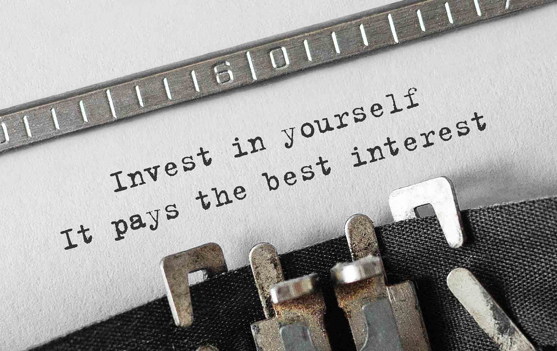Vintage typewriter with the words 'Invest in yourself — It pays the best interest' on the page.