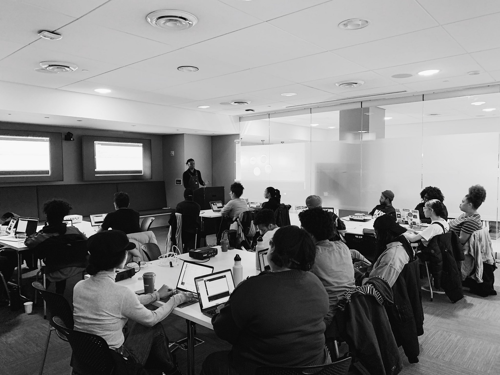 Black & white photo of a classroom filled with two dozen students at laptops. A Black man teaches at the front of the class.