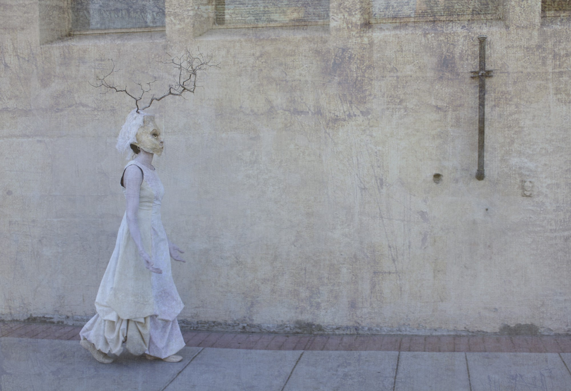 A masked figure in white walk along an old, wall, textured in shades of off-white and beige.