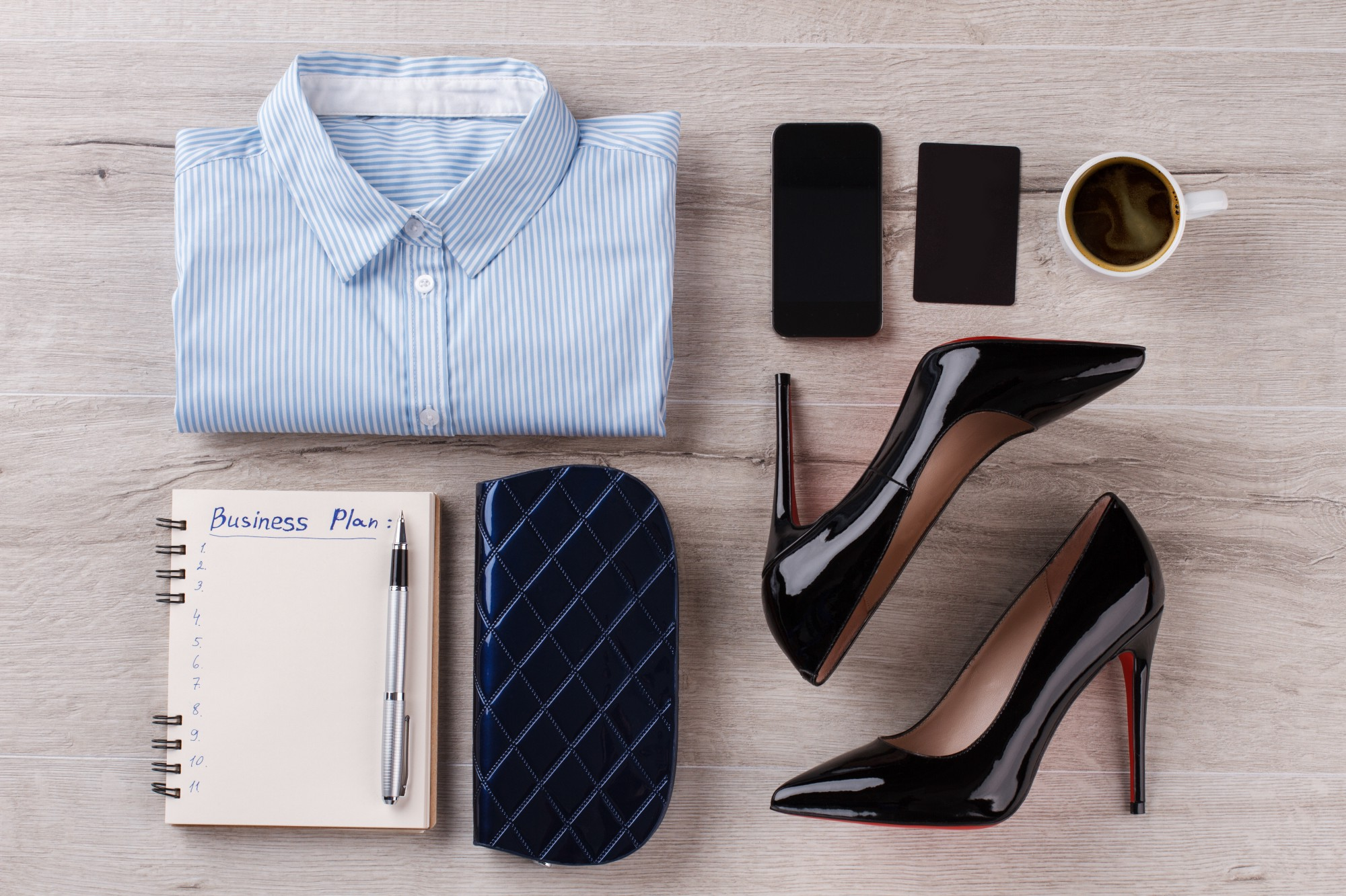 Shirt, notebook with pen. Office woman's flatlay on wooden table. Look in dark shades.