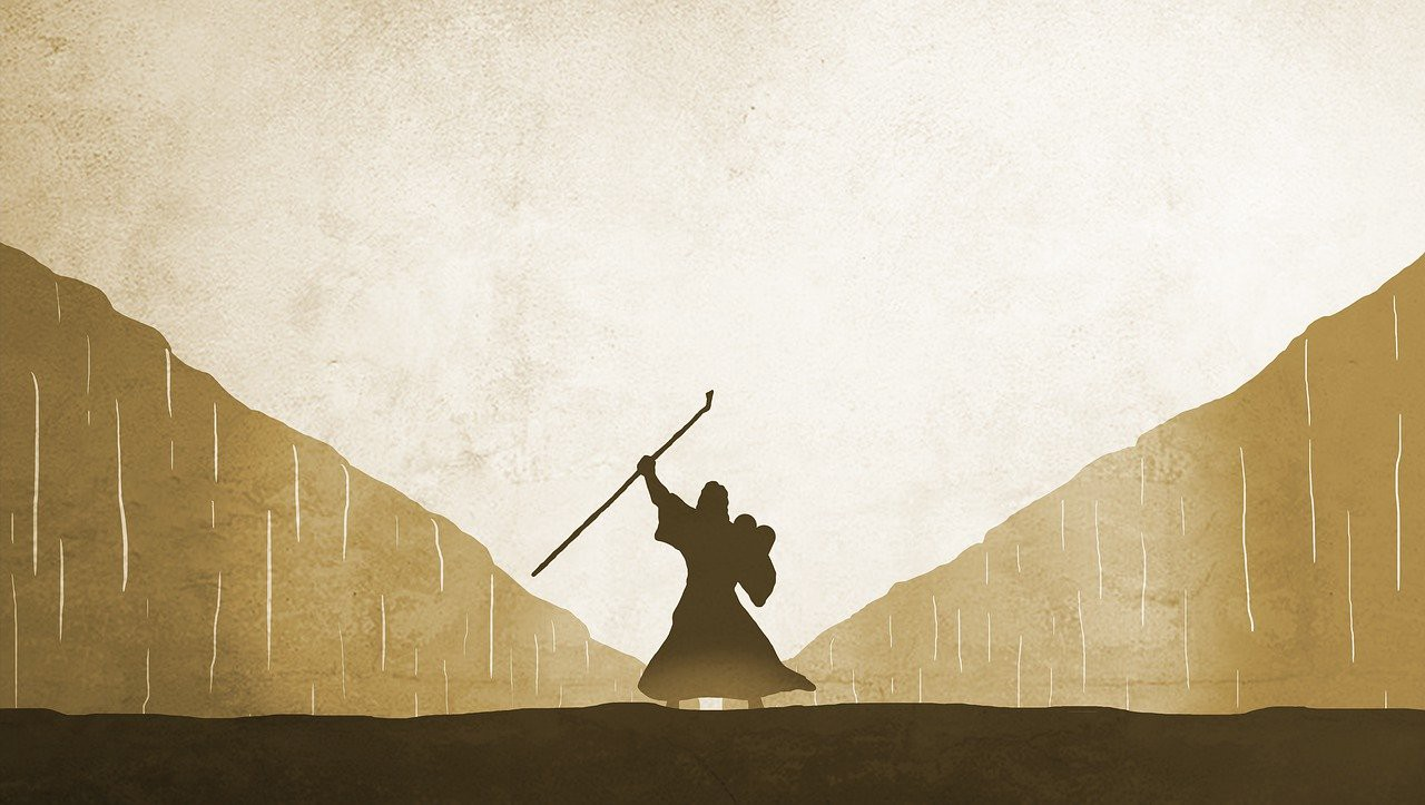 A silhouette image of Moses standing in the middle of the Red Sea.