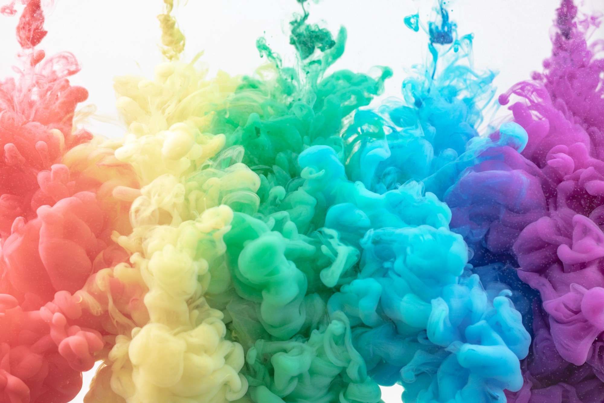 A splash of rainbow colors dissolving in water at the same time