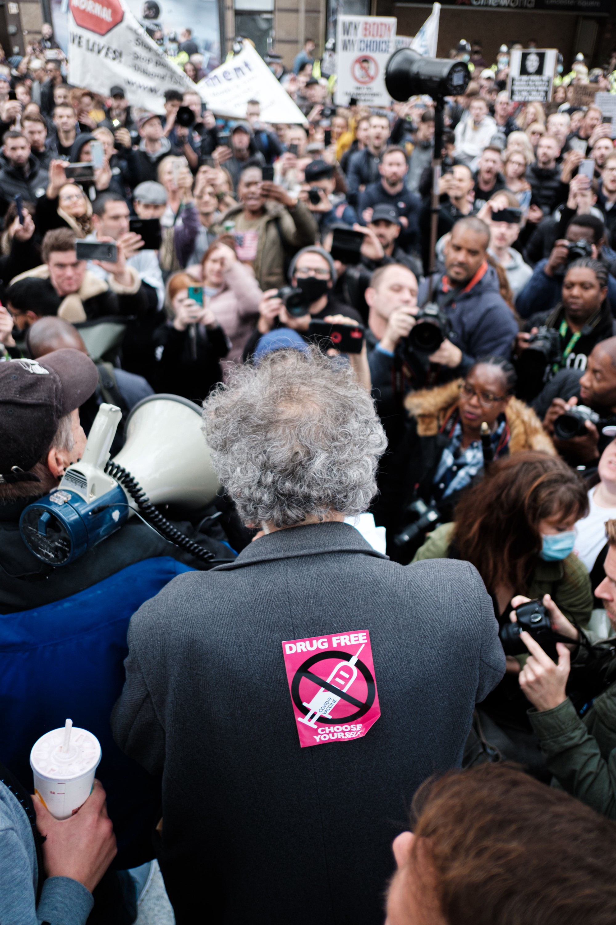 Man in front of a crowd, with his back to the camera, with an anti-vaccine sticker stuck to the back of his coat.