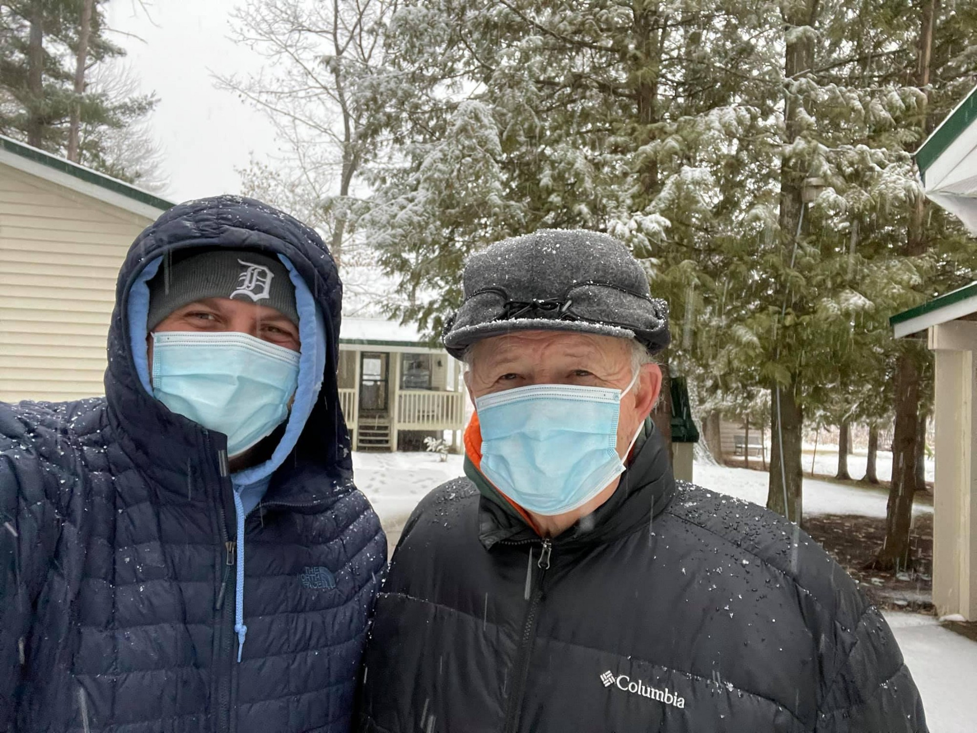 Father and son stand in front of the cabin while it's snowing dressed in winter coats, hats, and surgical masks.
