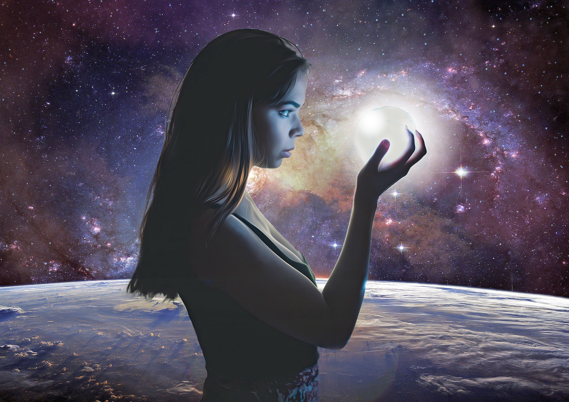 Girl holding a ball of light with space background.