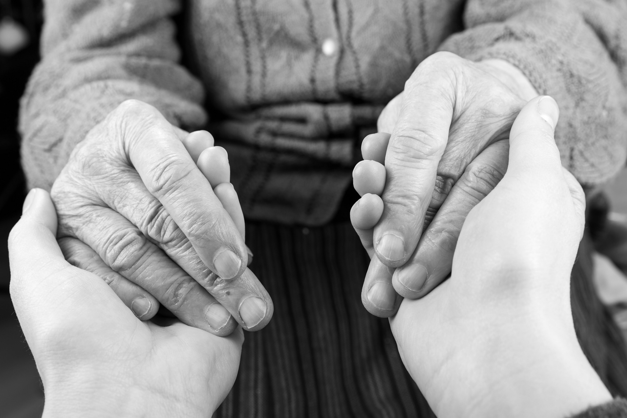 Hands of a young person holding those of  an older person. Photo by Obencem/Getty Images