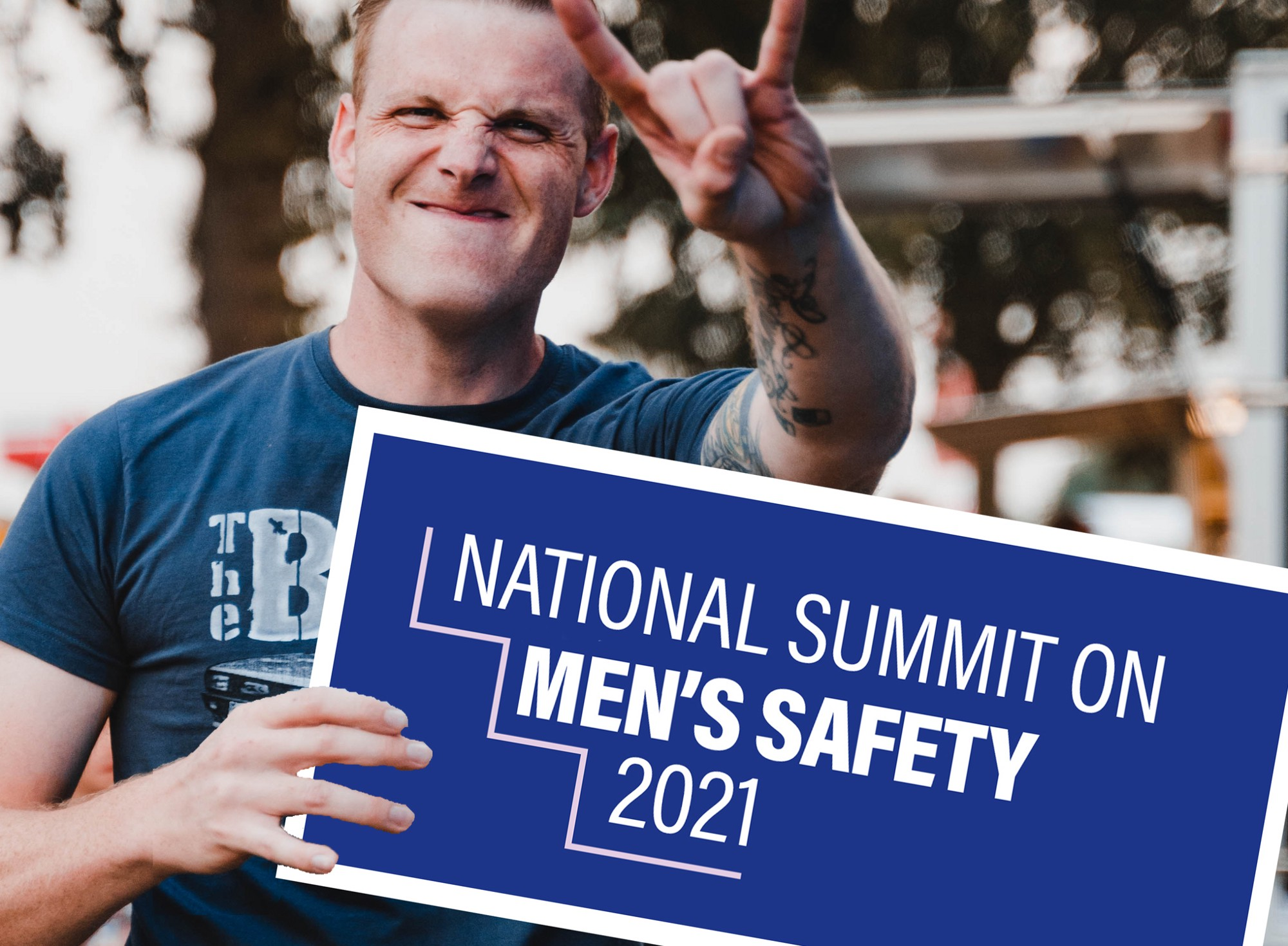 A young white man holds a sign for a Men's Safety Summit while holding his hand up in the rock on gesture.