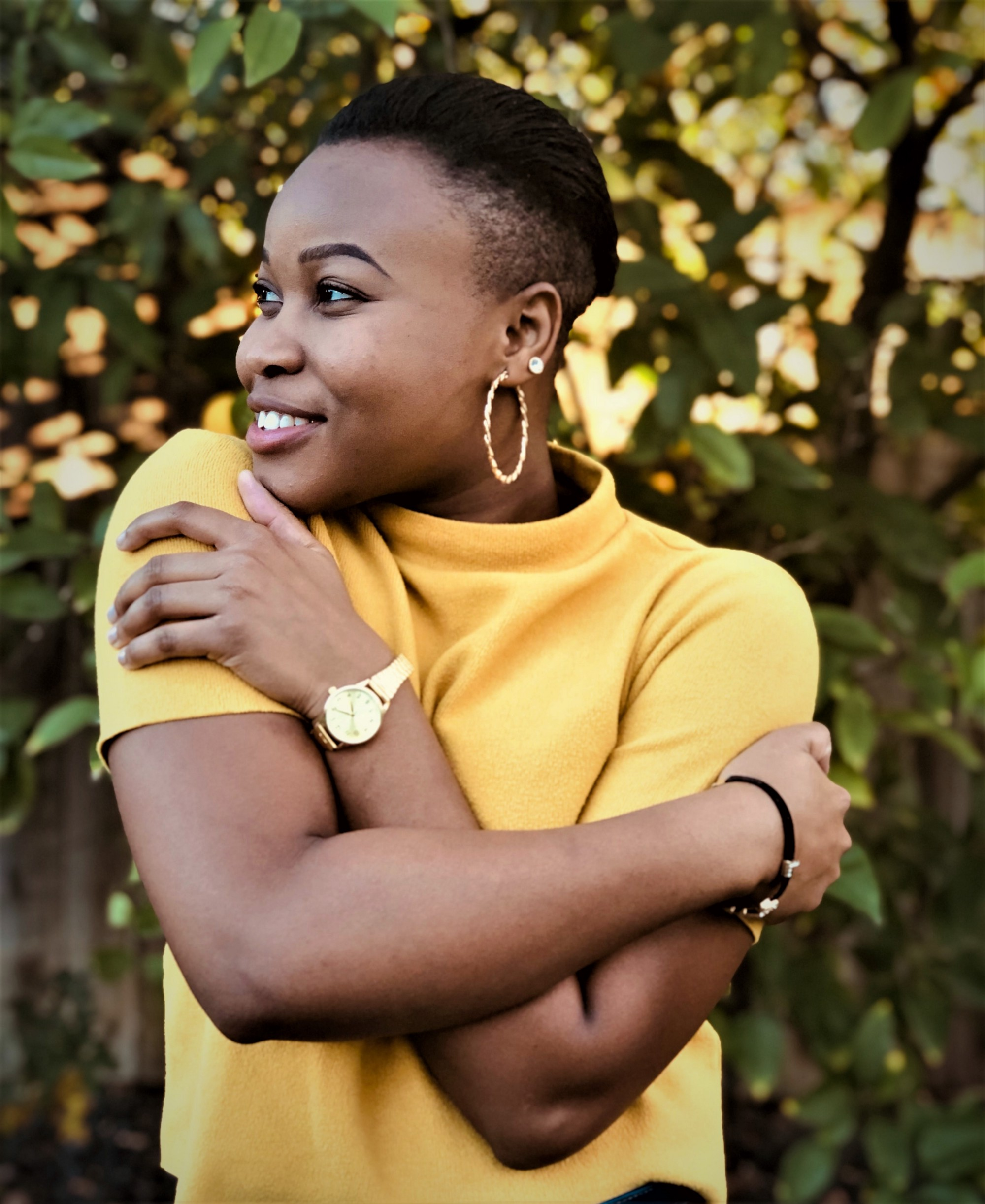Happy woman wearing short-sleeve yellow top and gold watch hugging herself green leafy background