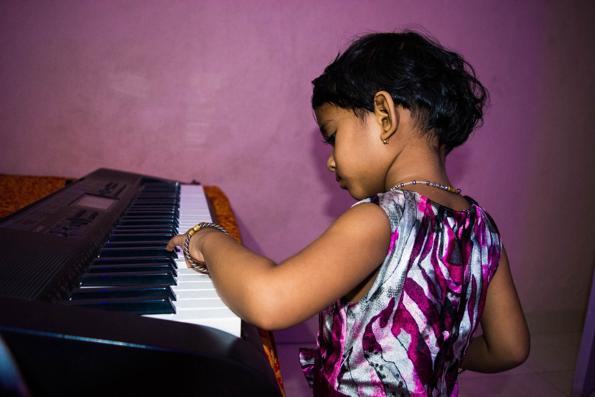 Cute child of color playing the piano