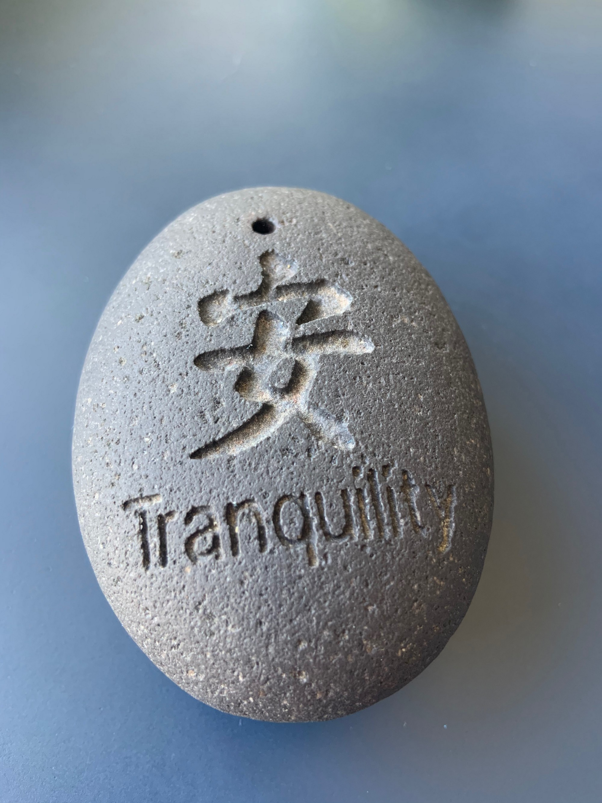 """oval stone with the word """"Tranquility"""" and a Chinese character engraved on it."""