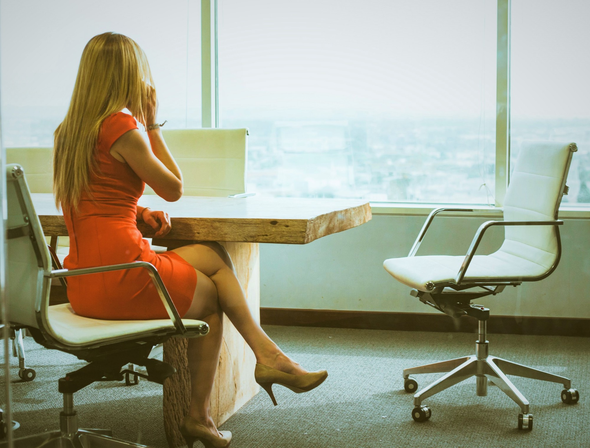 woman with long blonde hair sitting at conference table looking out over city with phone held to her ear